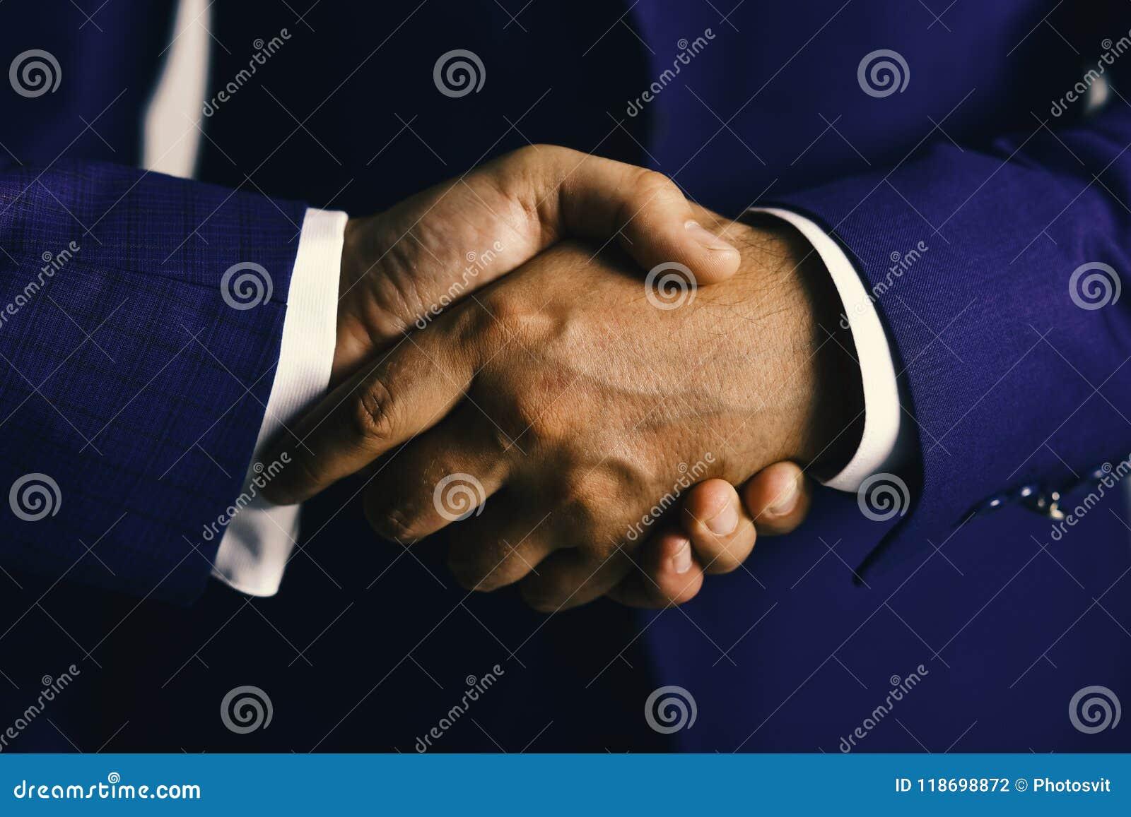 商人穿着聪明的衣服 生意和协议概念 紧紧震动男性的手 在浅灰色的握手