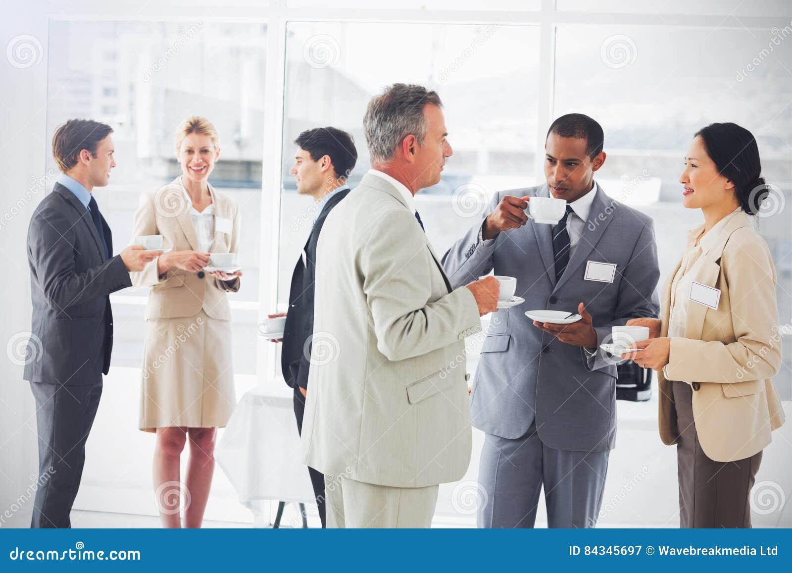 商人聊天的和饮用的咖啡在会议