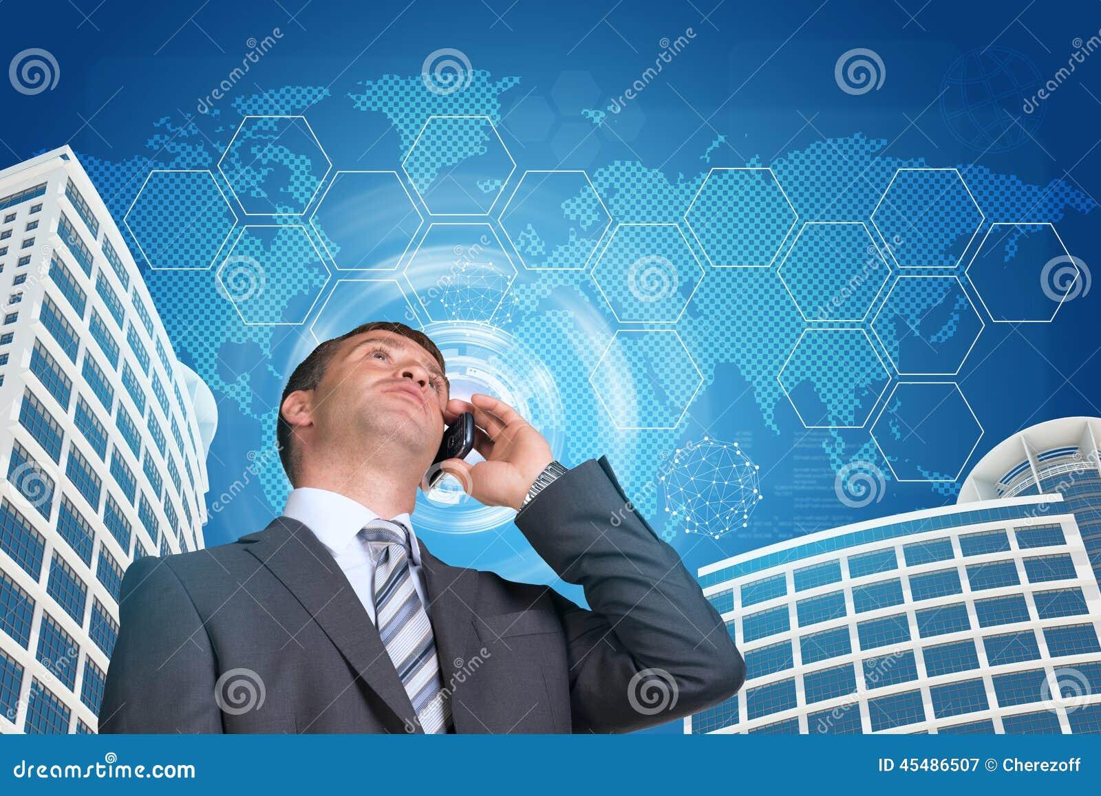 商人谈话在电话 摩天大楼,天空