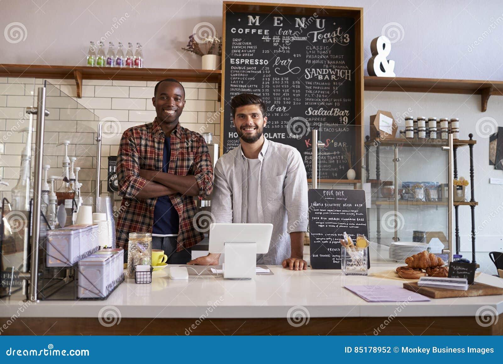 商务伙伴在柜台后站立在咖啡店