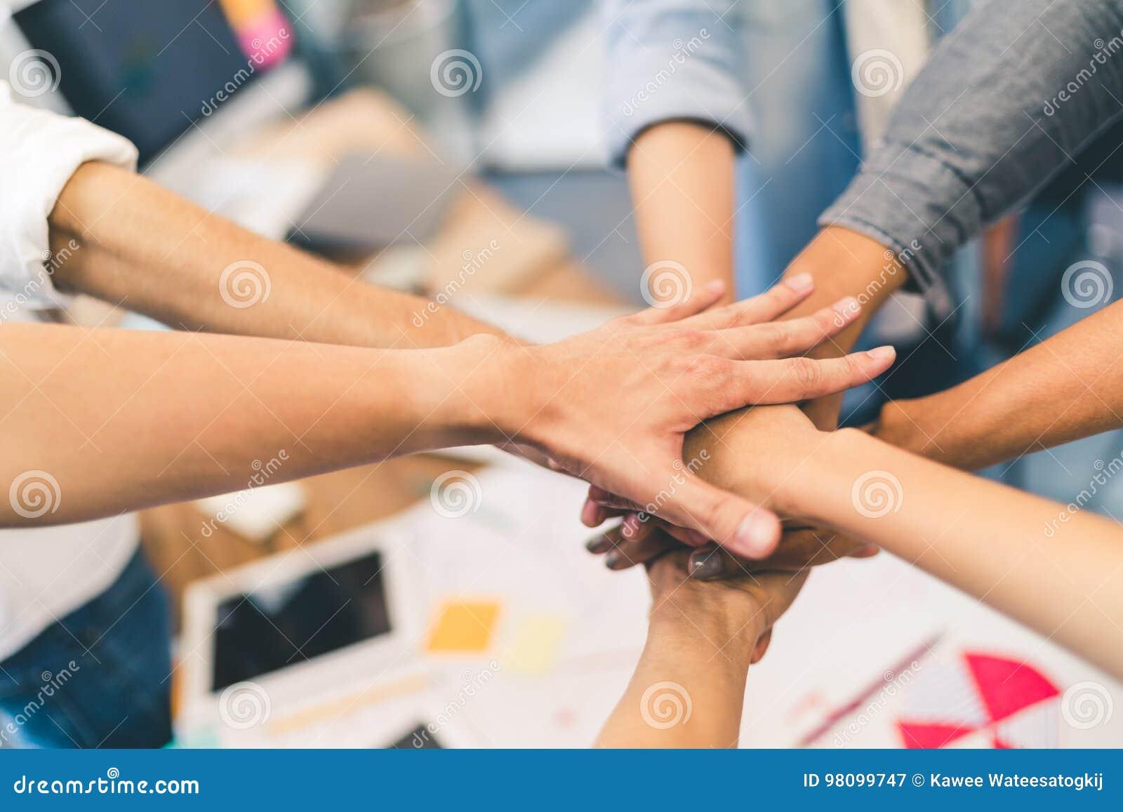商务伙伴配合或友谊概念 不同种族的不同的小组同事一起加入手
