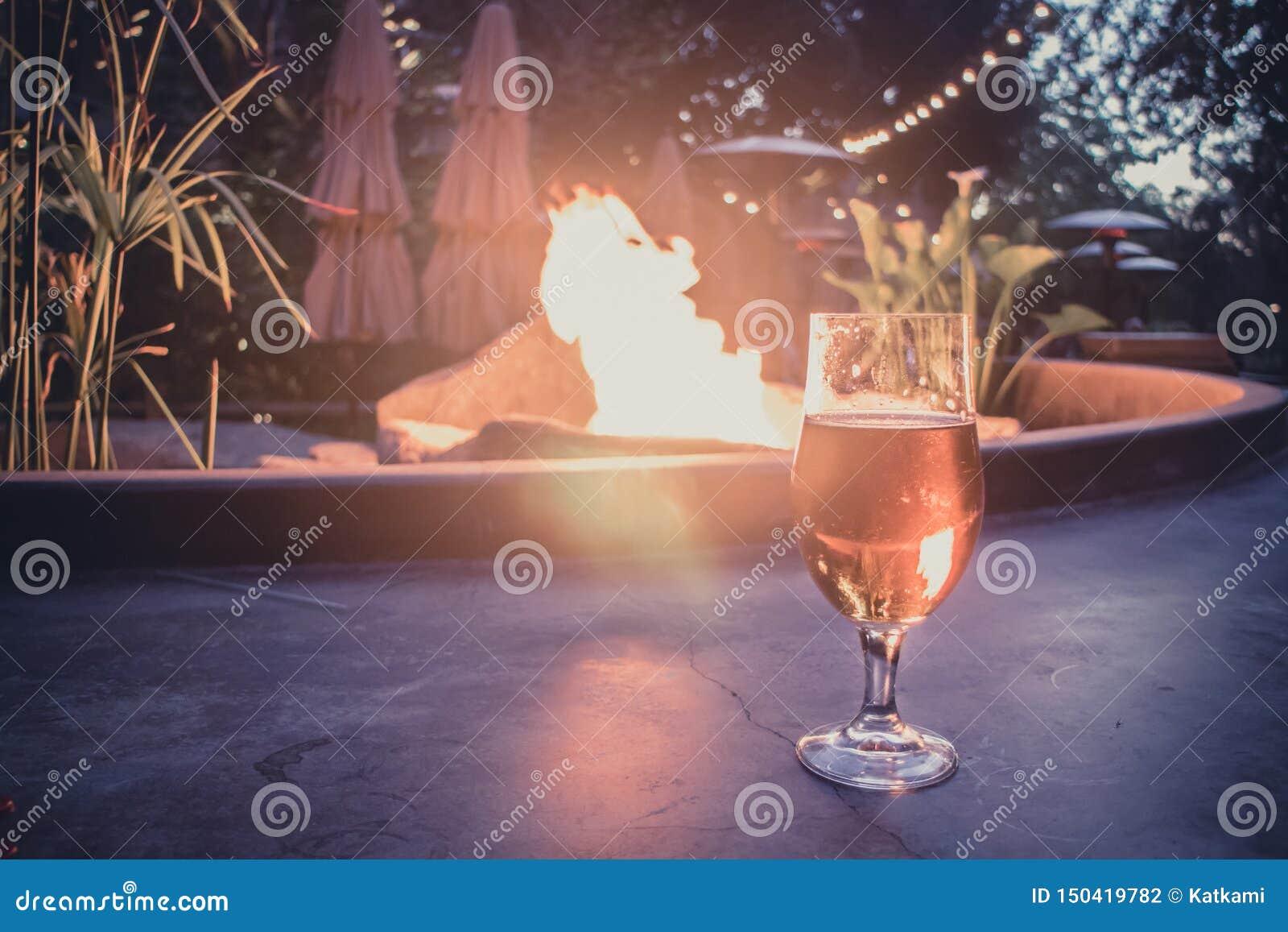 啤酒杯由火坑在背景中照亮了