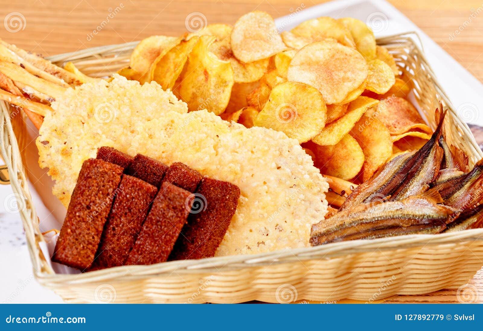 啤酒的被分类的快餐:各式各样的鱼,土豆片,盐味的薄脆饼干,在篮子的黑麦面包油煎方型小面包片