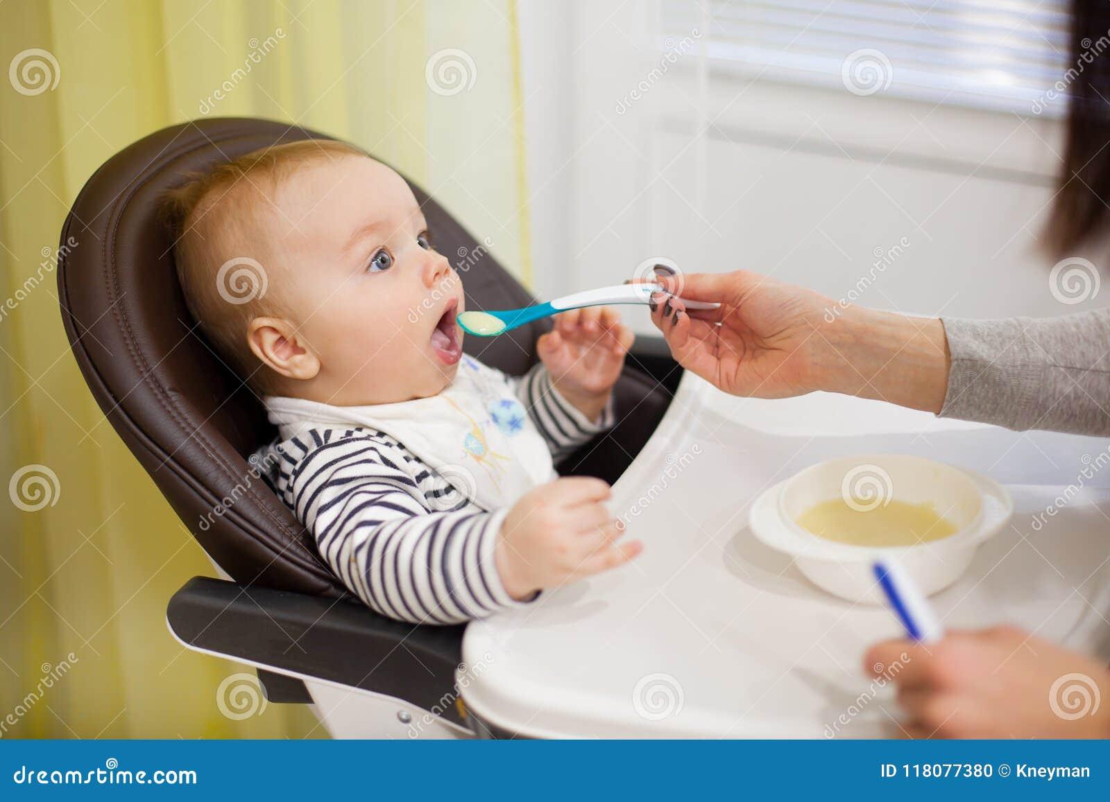 喂养她的小小儿子用粥的年轻母亲,坐在哺养的高婴孩椅子