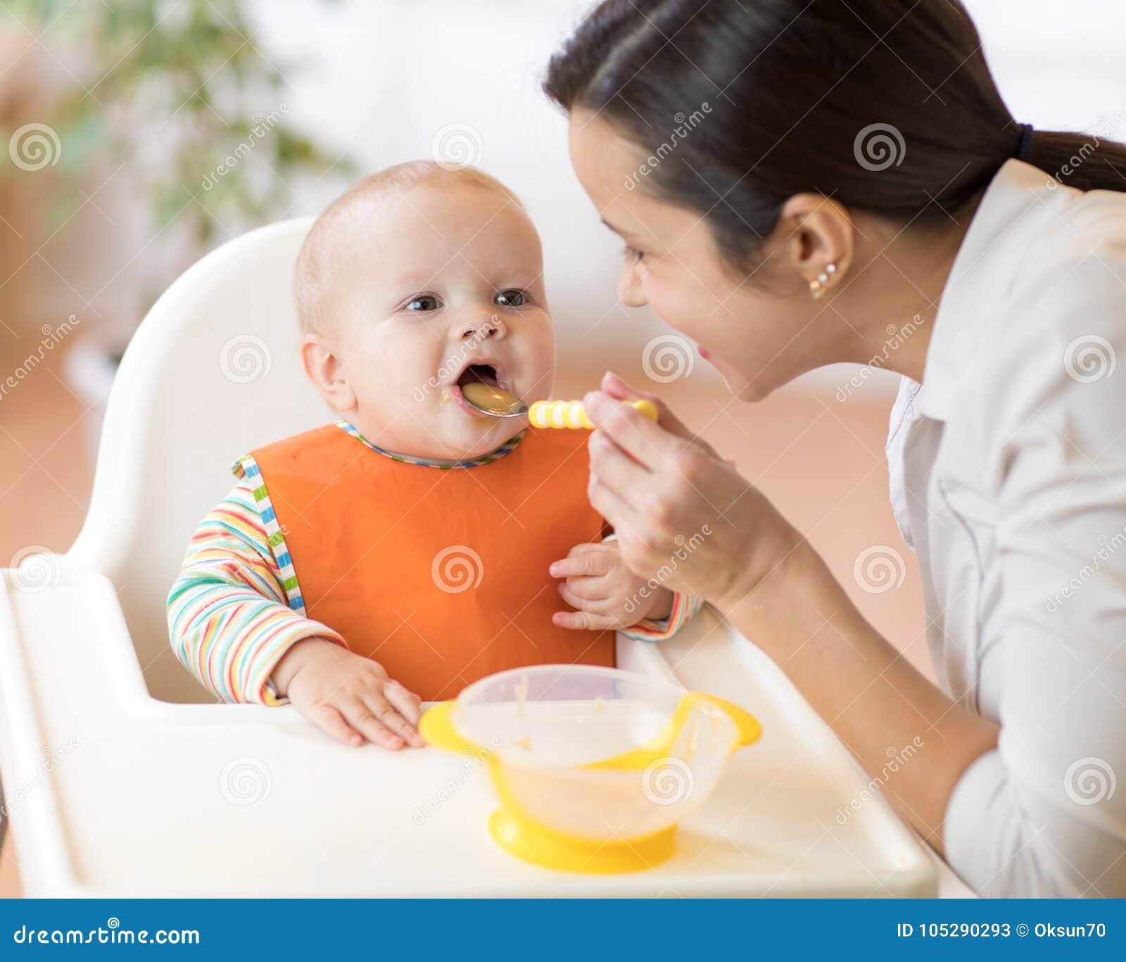喂养她的有匙子的母亲婴孩 照顾在家给健康食物她可爱的孩子