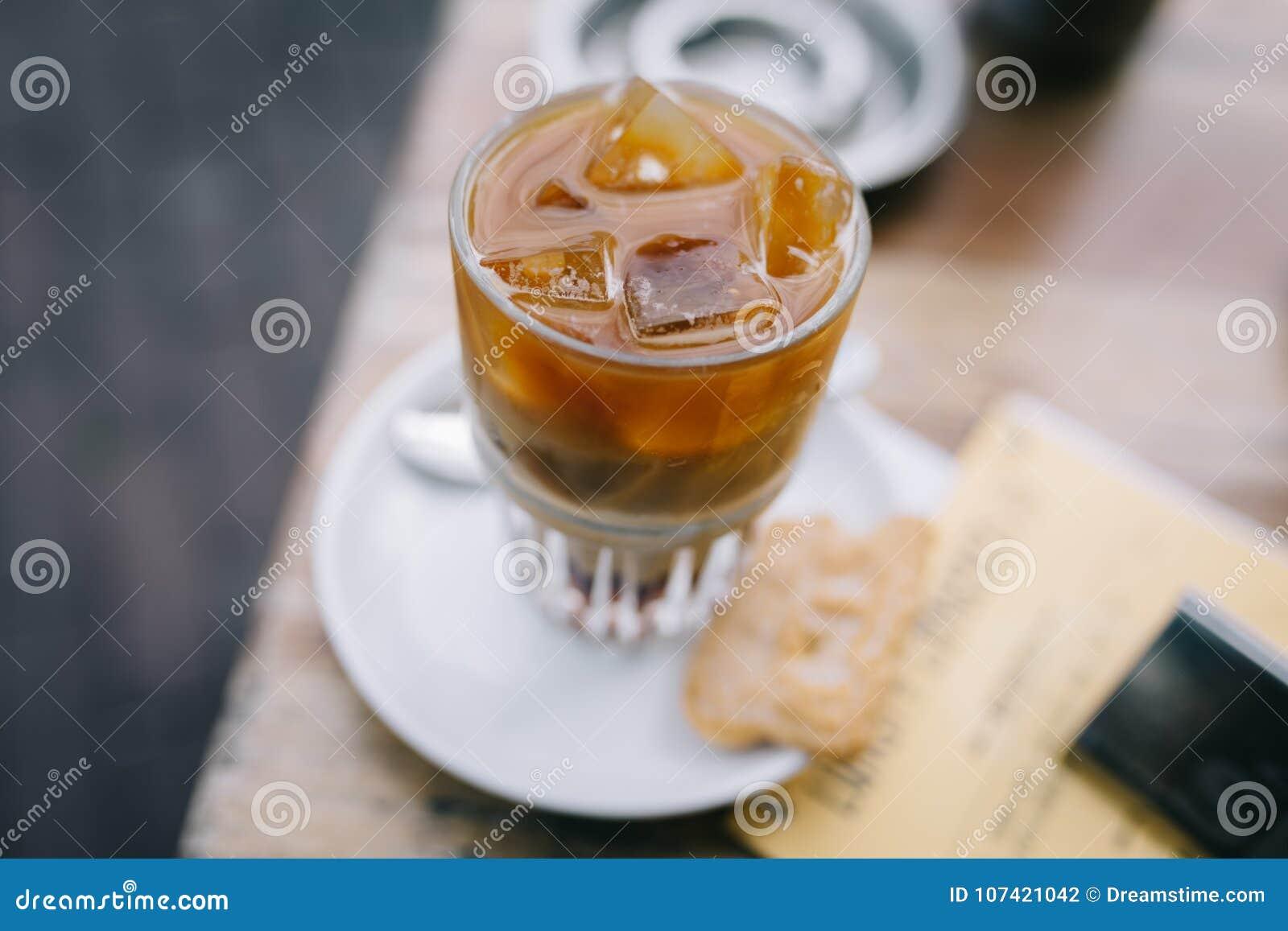 喝一份被冰的咖啡在与拿铁的夏天在一张木桌上