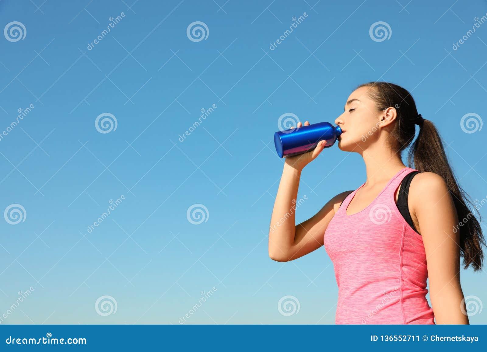 喝从水瓶的年轻运动的妇女户外在好日子