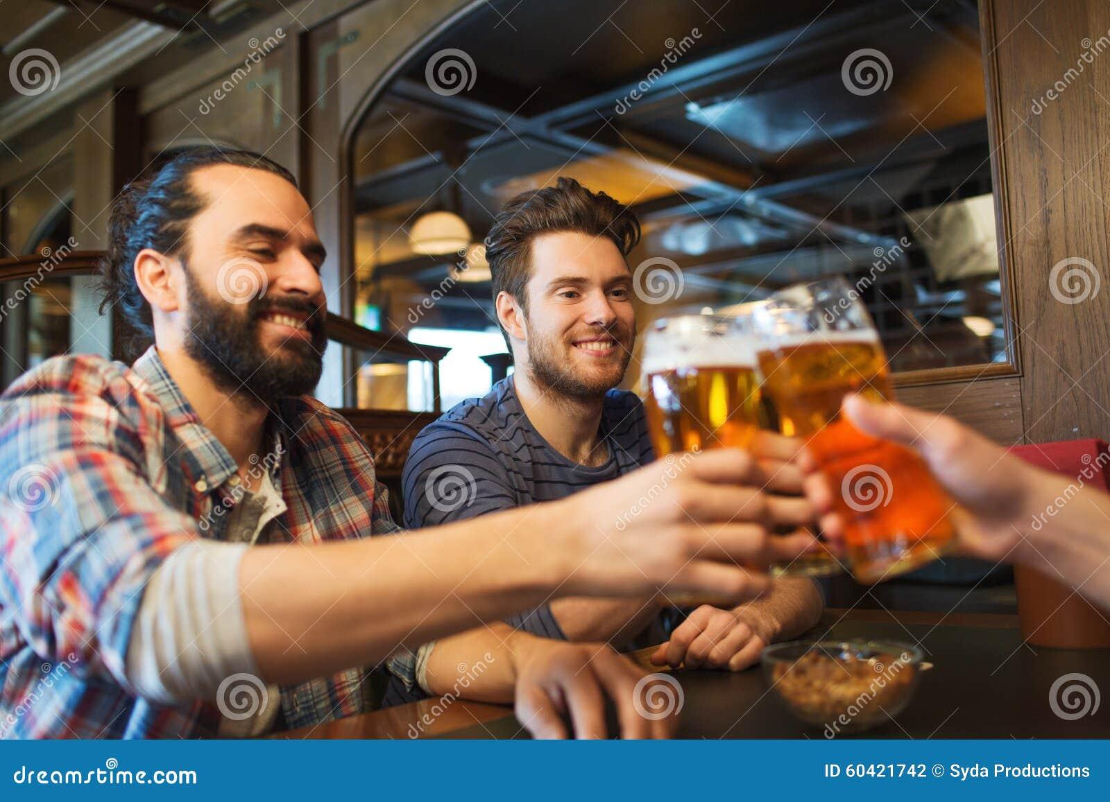 喝啤酒的愉快的男性朋友在酒吧或客栈