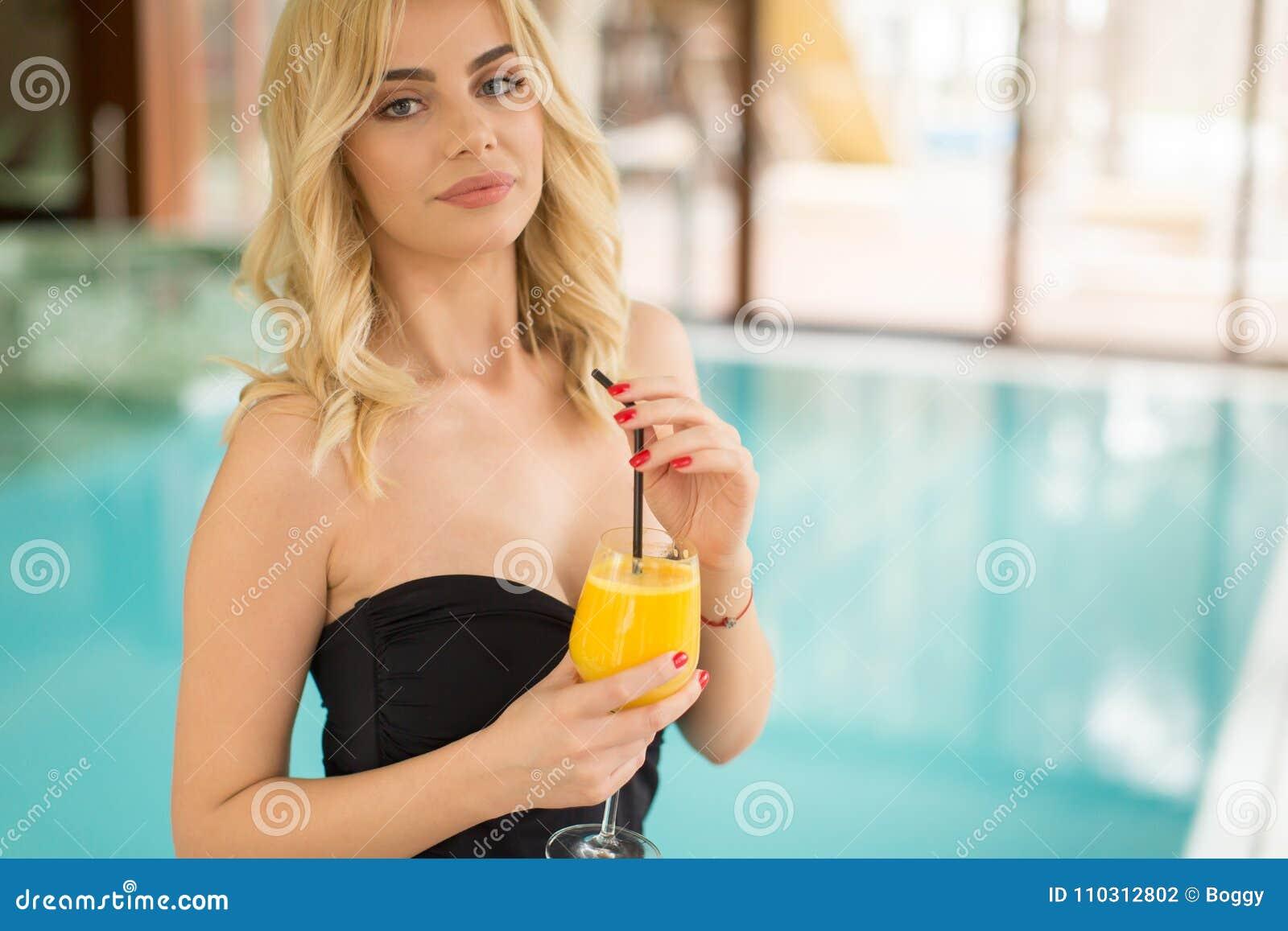 喝在游泳池边的美丽的年轻女人画象汁液