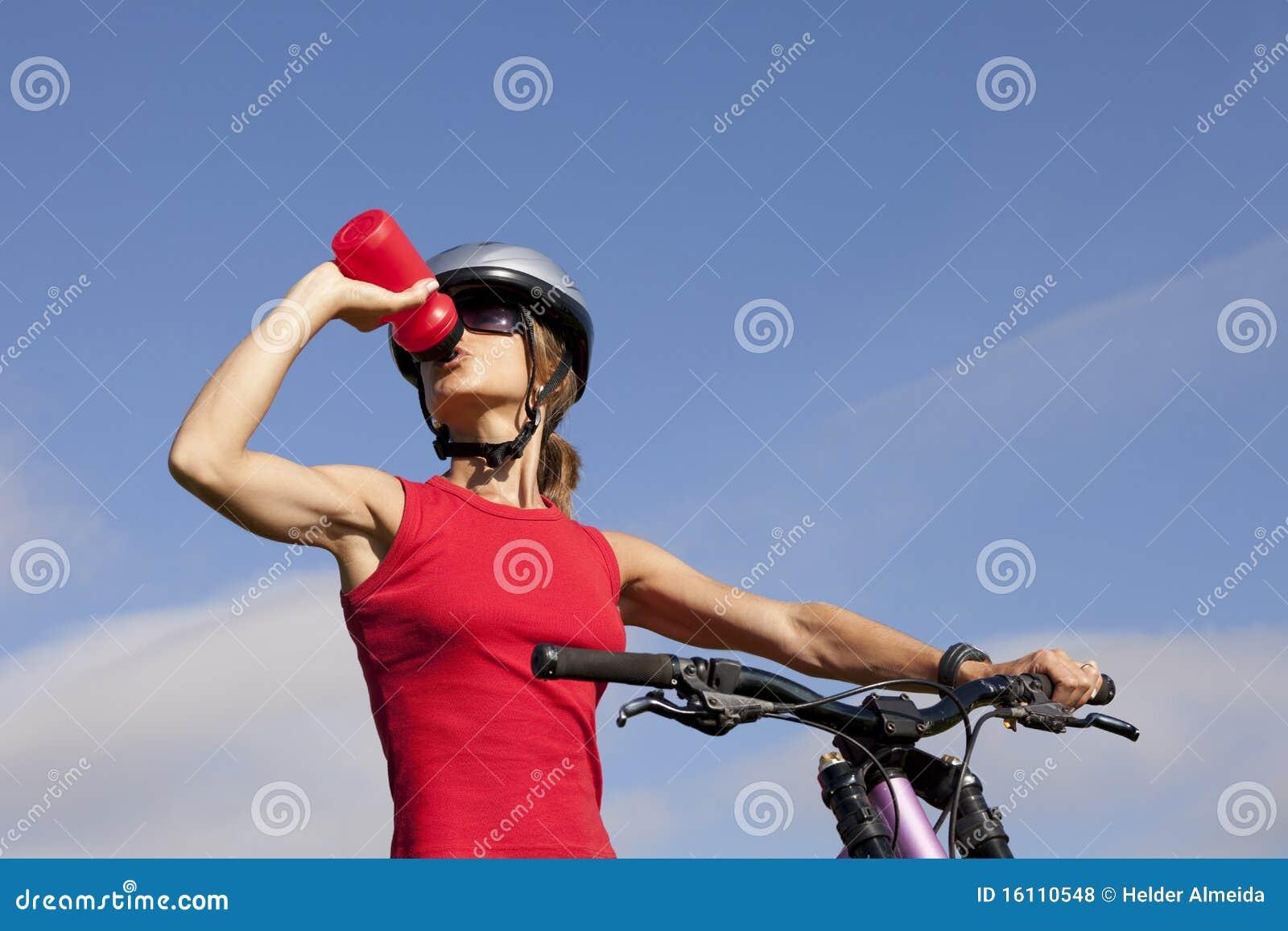 喝她的水妇女的自行车