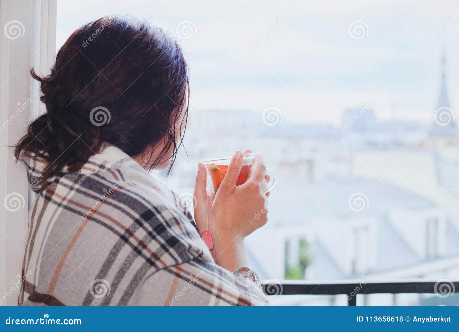 喝热的茶和在家看窗口,舒适冬天的妇女