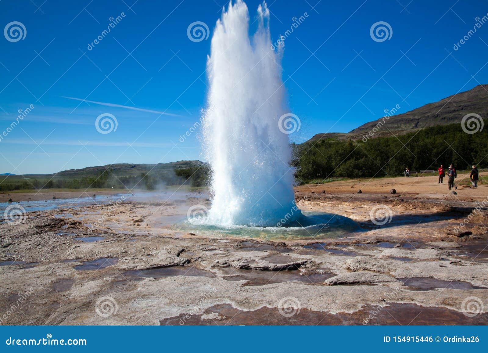 喷泉Strokkur在反对天空蔚蓝和森林A小组的冰岛未知的游人