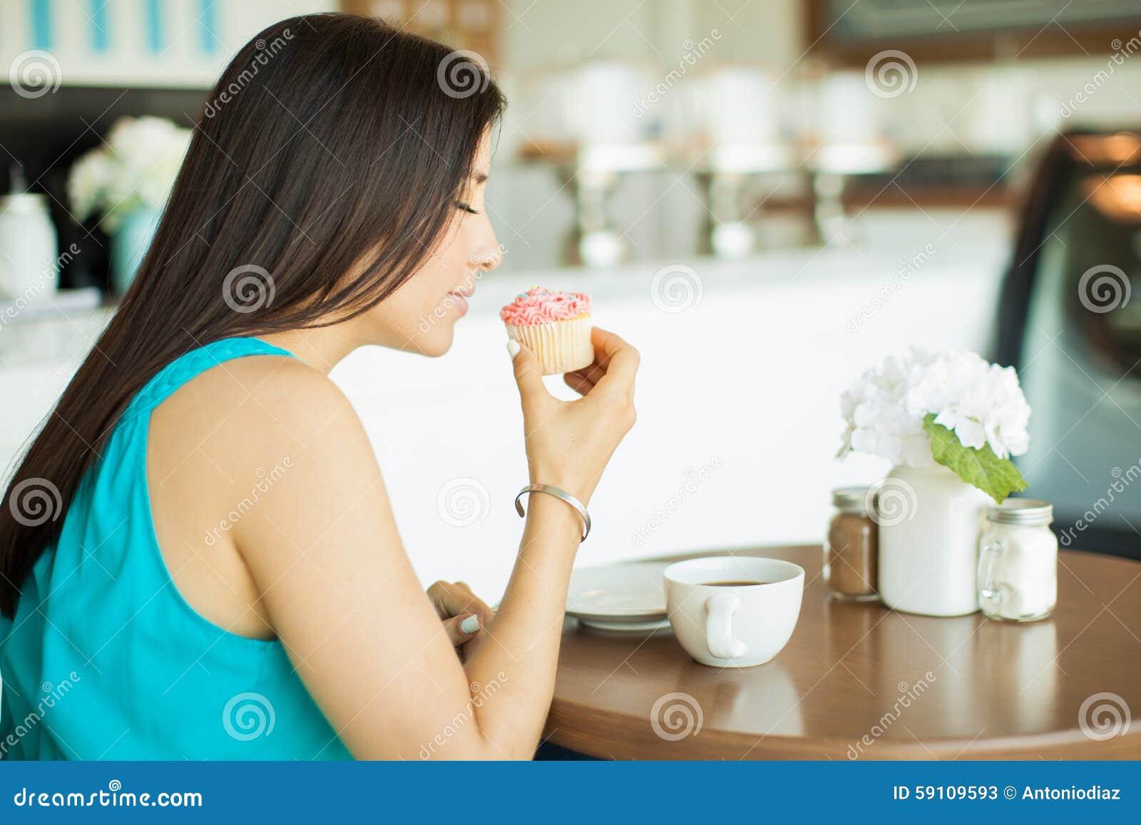 嗅到杯形蛋糕的少妇