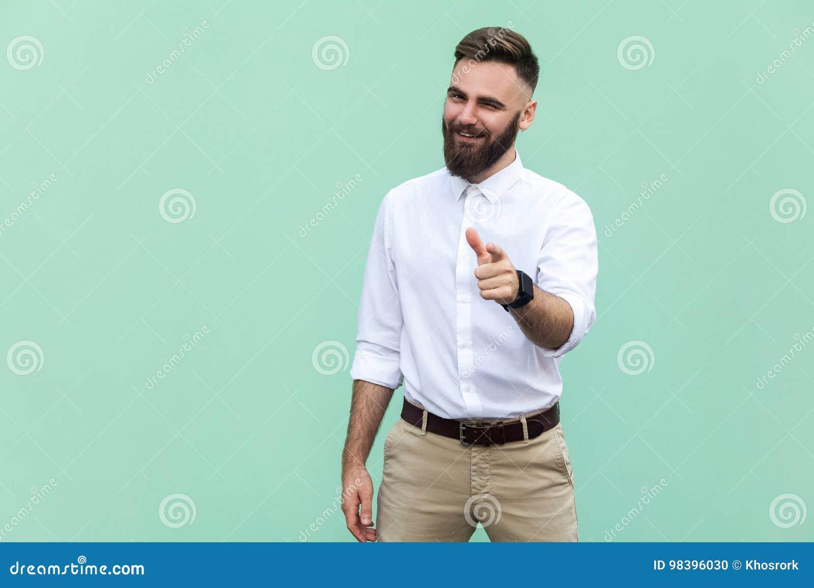 嘿您!年轻成人有胡子的人,指向手指和看照相机 在浅绿色的背景 室内