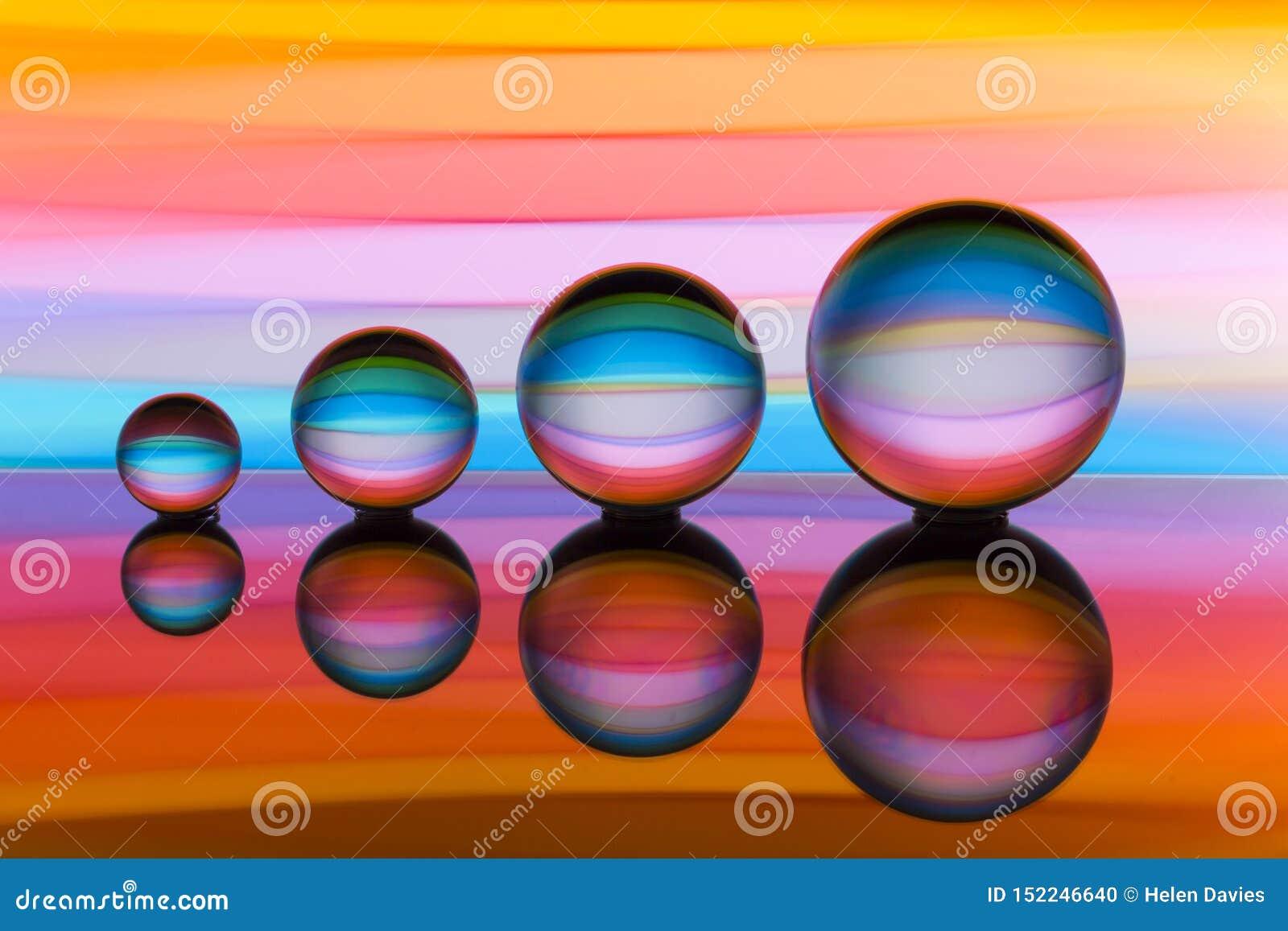 四个水晶球连续与彩虹颜色五颜六色的条纹在他们后的