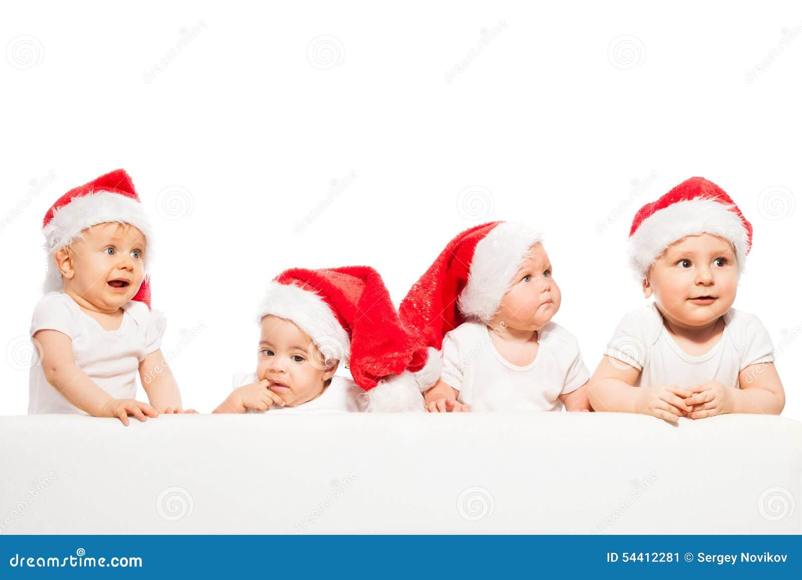 四个婴孩连续站立穿戴红色圣诞节帽子