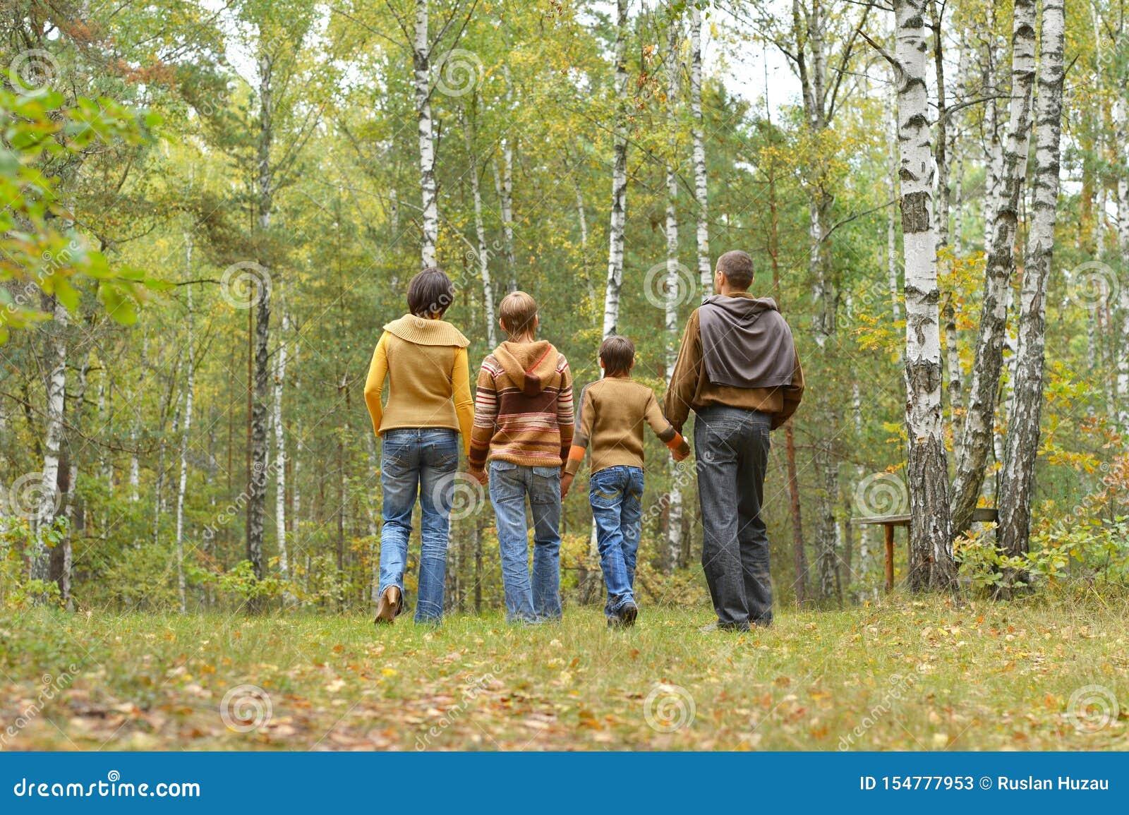 四口之家画象获得乐趣在秋天森林