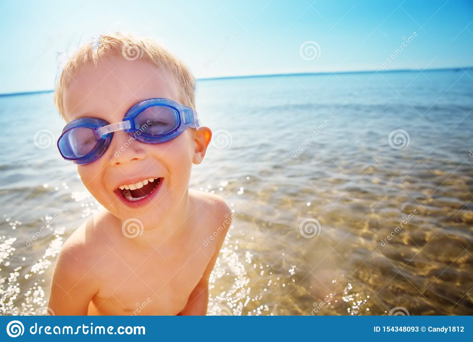 四岁使用在与游泳的玻璃的海滩的男孩