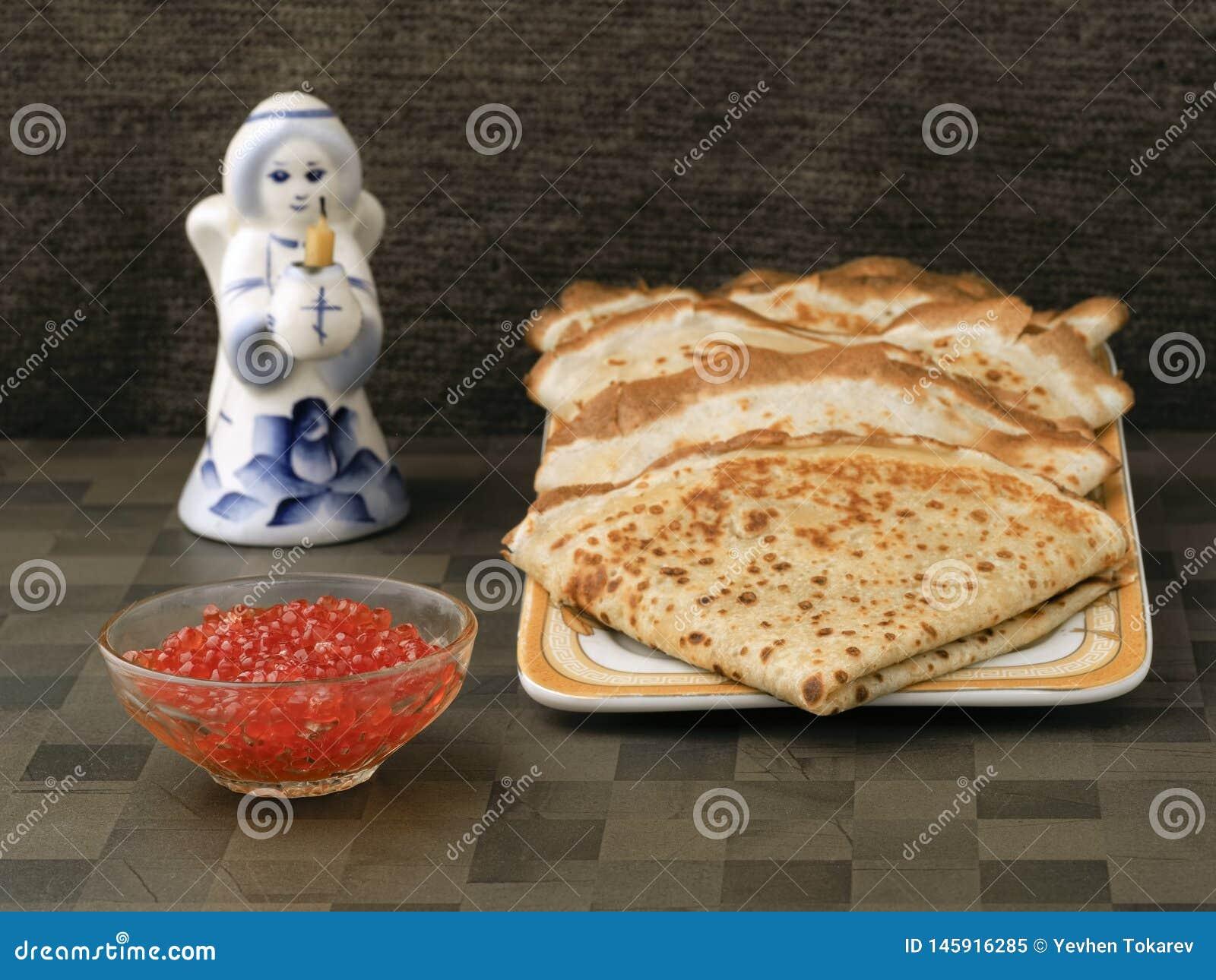 四整洁红润薄煎饼在板材碗用红色鱼子酱 举一个教会蜡烛的天使的下个图