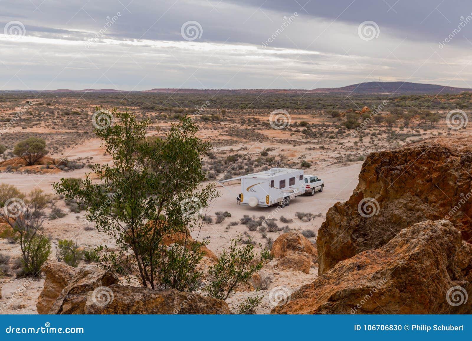 四轮驱动的车和大白色有蓬卡车在岩石露出旁边野营