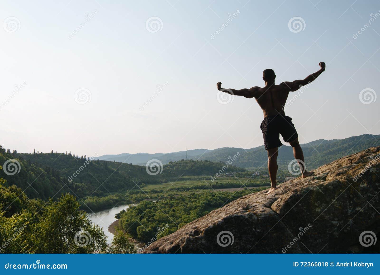 回到视图 非裔美国人的运动人剪影有摆在岩石的赤裸躯干的 绿色山自然