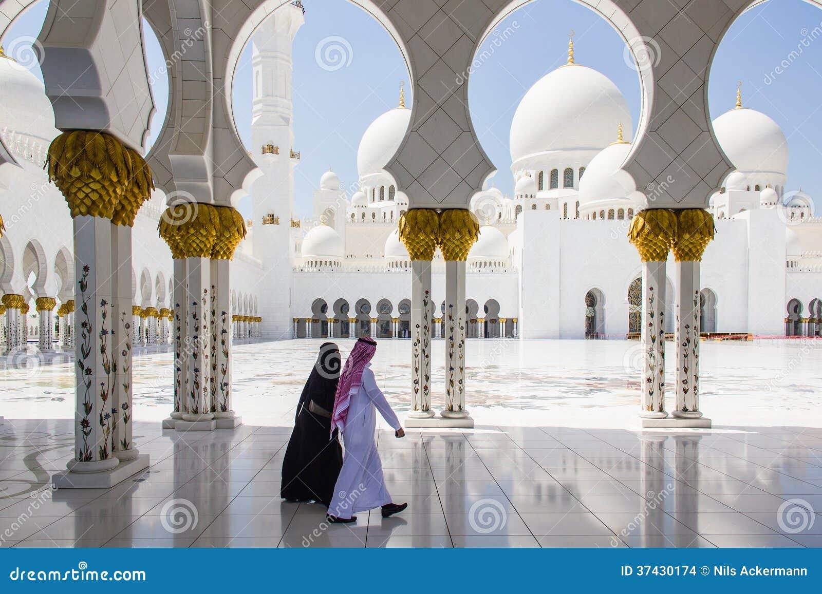 回教走在扎耶德Grand Mosque回教族长的男人和妇女采取2013年3月31日在阿布扎比,单位