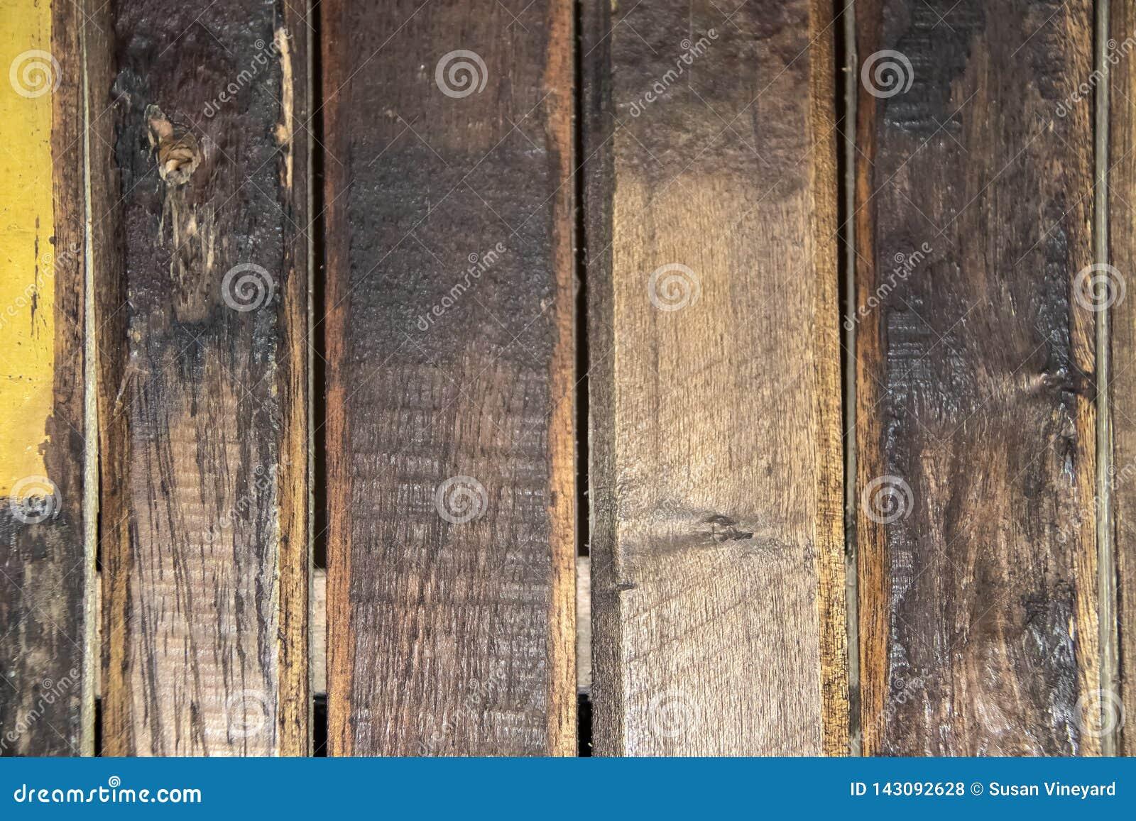 困厄的垂直的木板条背景与在绘以黄色污点