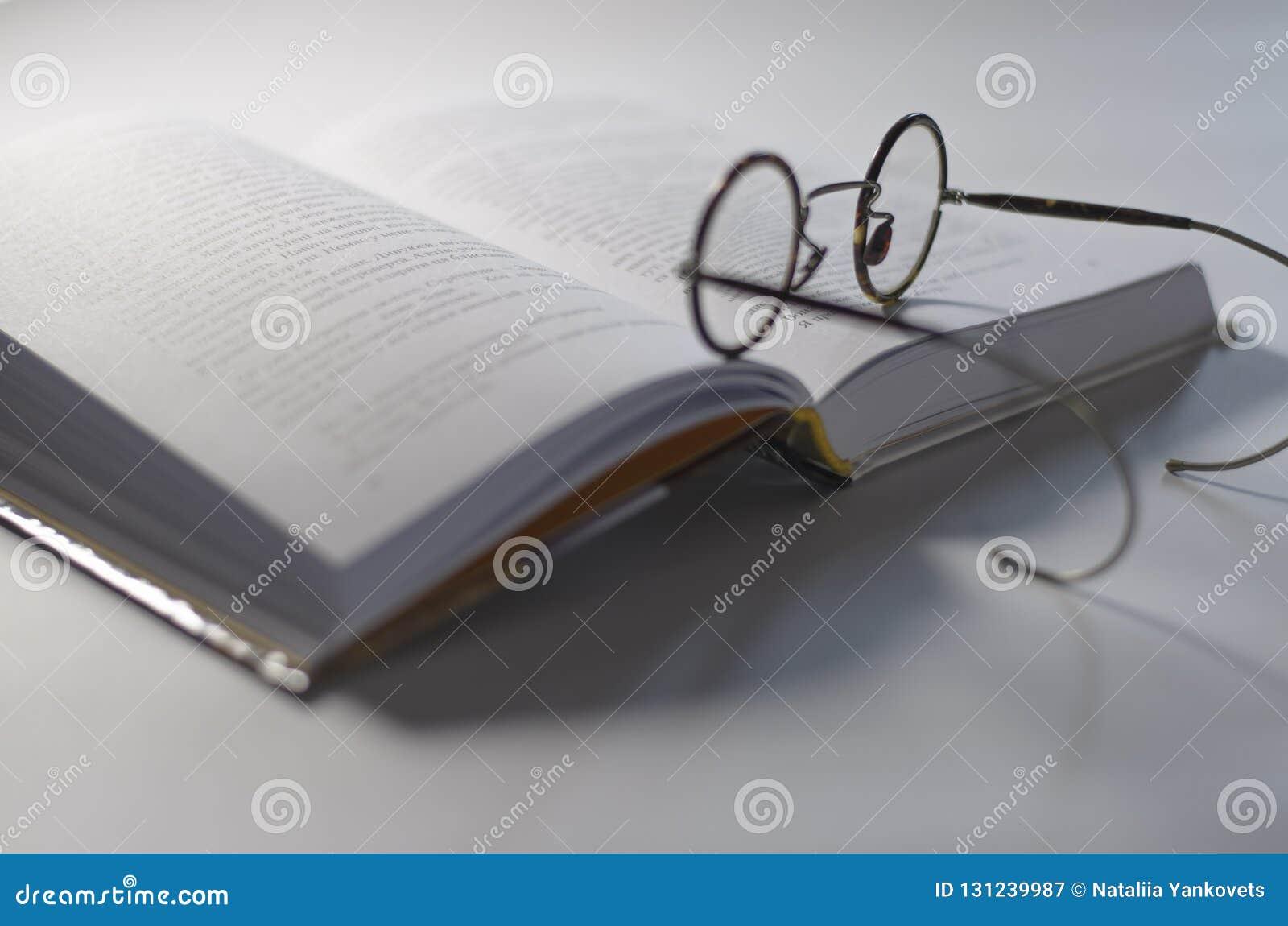 围绕老玻璃放置在一本开放白皮书,在白色背景说谎