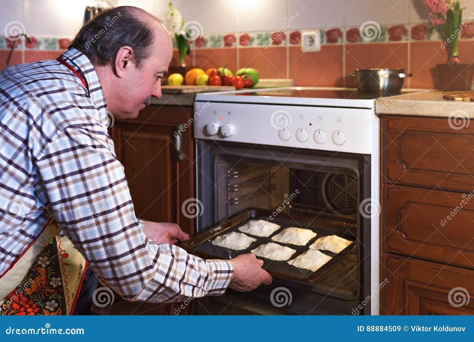 围裙的一个年长人准备饼