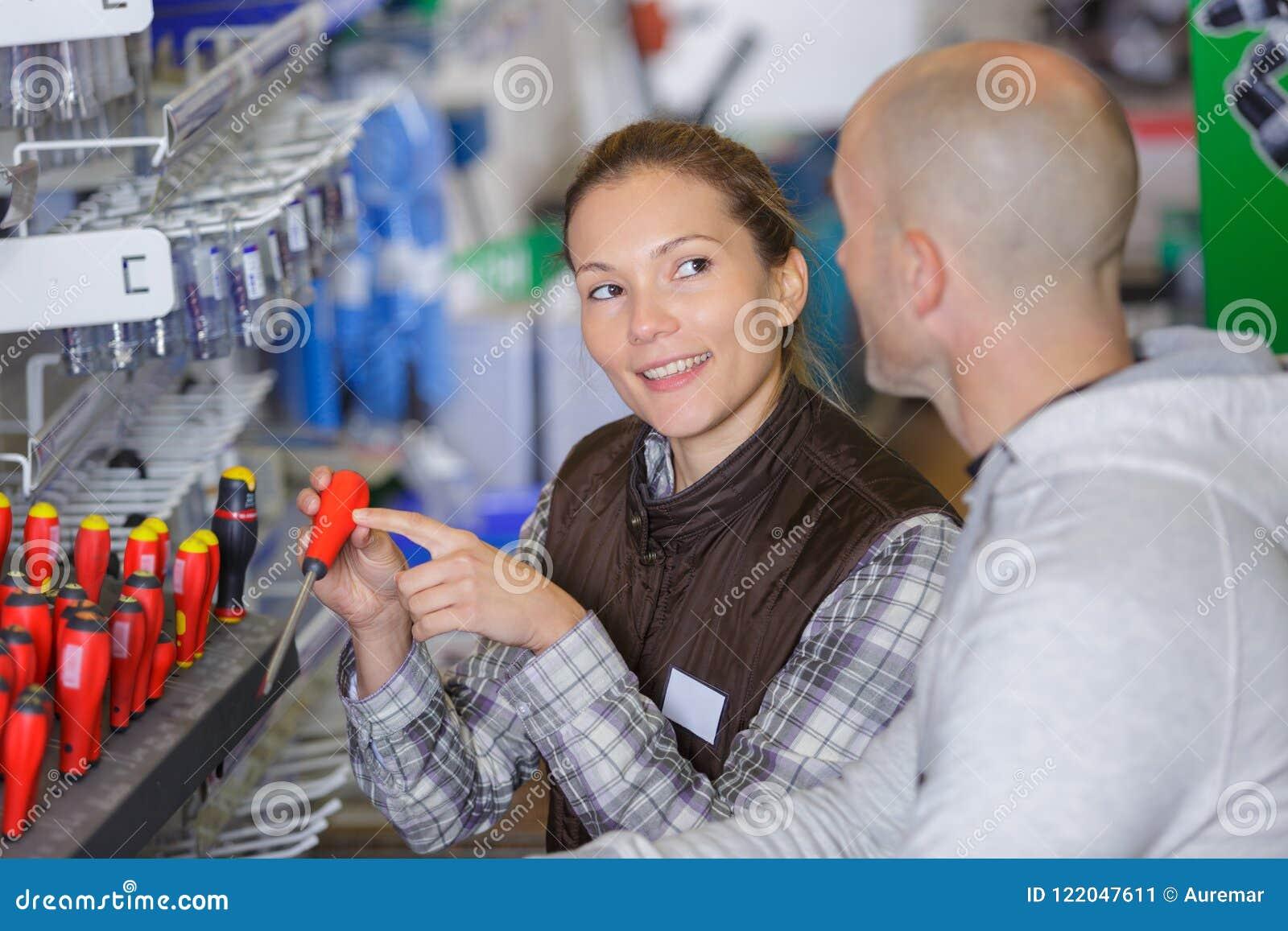 围裙的迷人的年轻女推销员与工具在超级市场