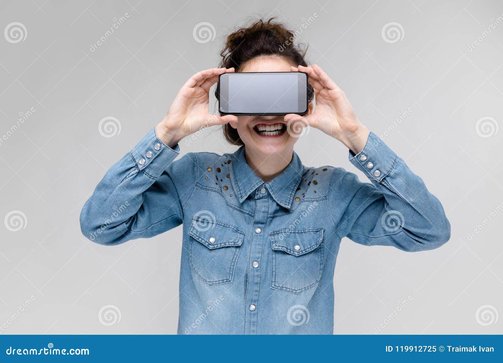 圆的玻璃的年轻深色的女孩 头发在小圆面包被会集 有一个黑电话的女孩 女孩盖了她的面孔