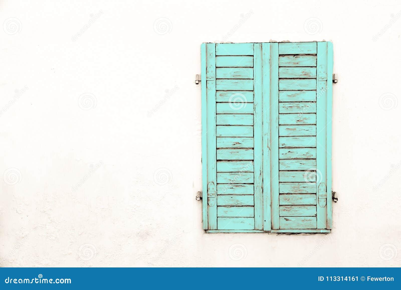 土气老脏和被风化的绿色深蓝木闭合的窗口关闭与削皮油漆