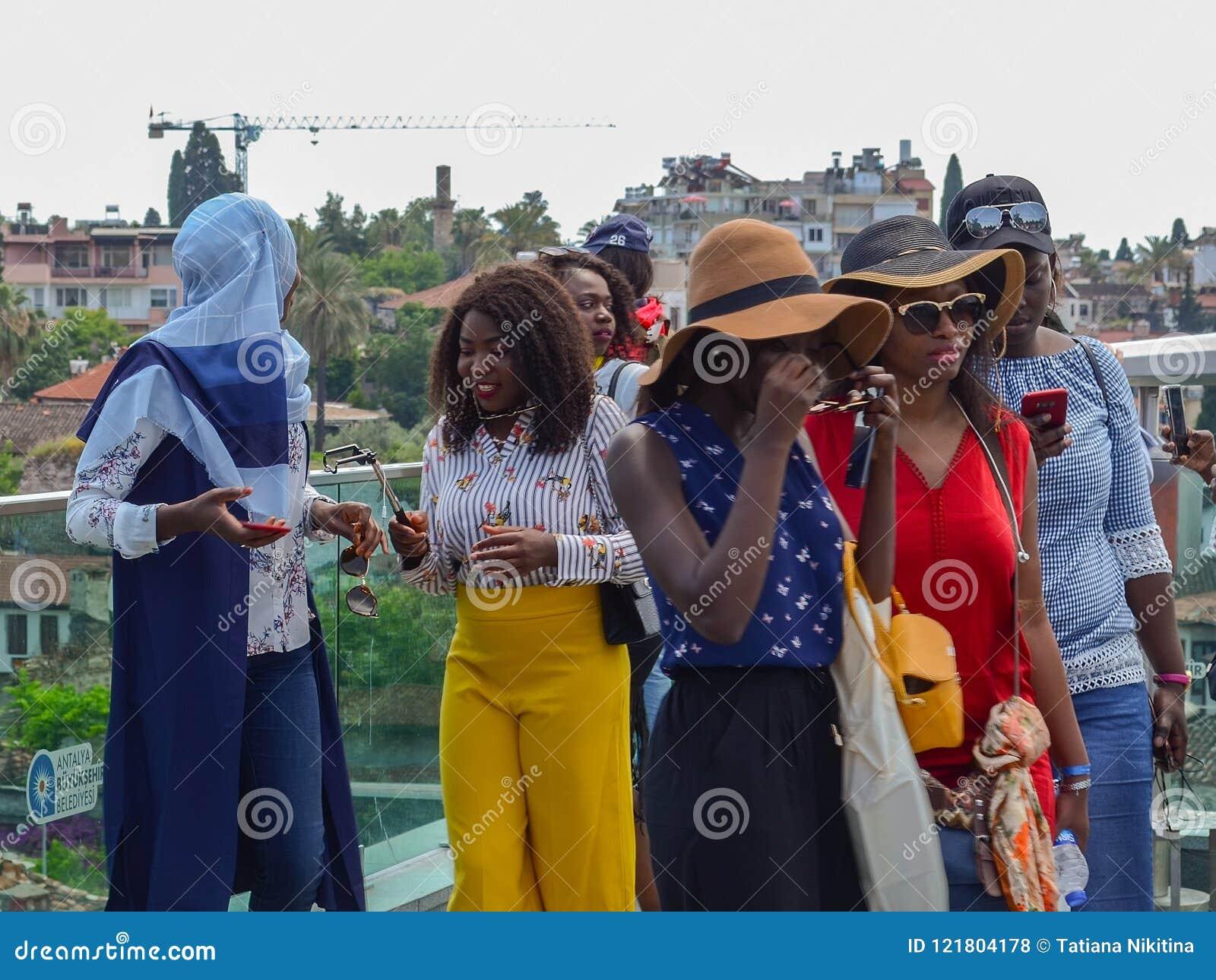 土耳其,安塔利亚, 2018年5月10日 小组明亮的衣裳的年轻非洲妇女在观察平台在检查t的老城市