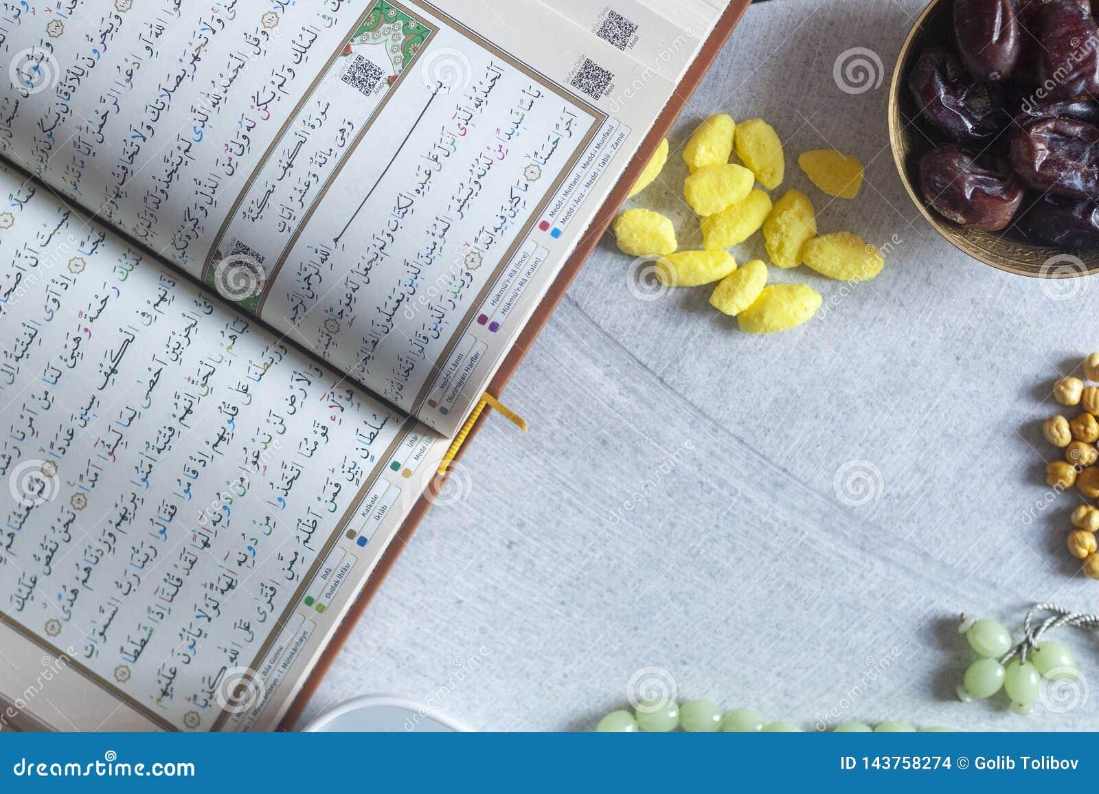 圣洁古兰经、念珠,Iftar甜点和干果子与一杯水 在视图之上 平的位置照片