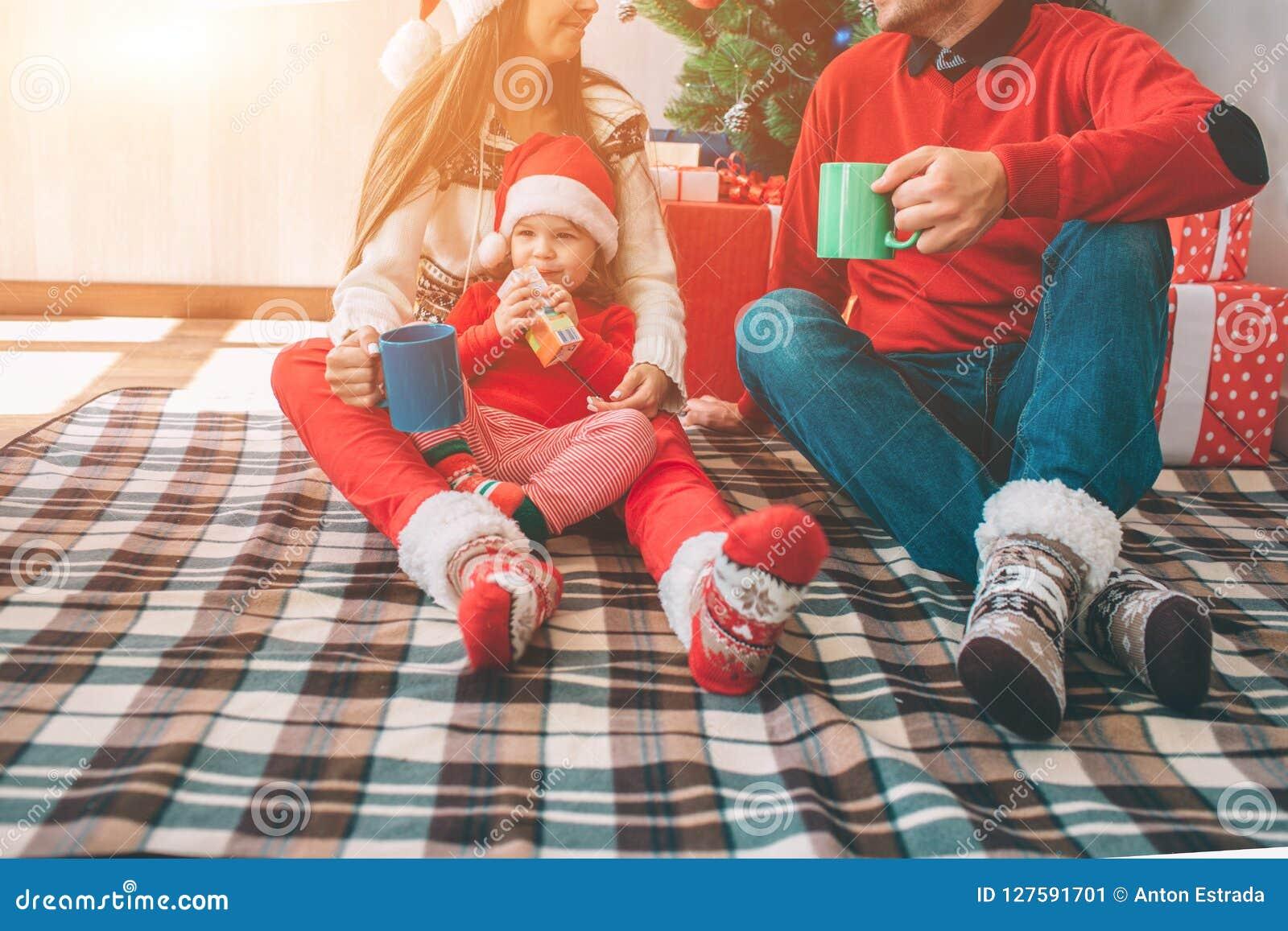 圣诞快乐和新年好 削减观点的家庭一起坐毯子 他们穿五颜六色的衣裳 人和