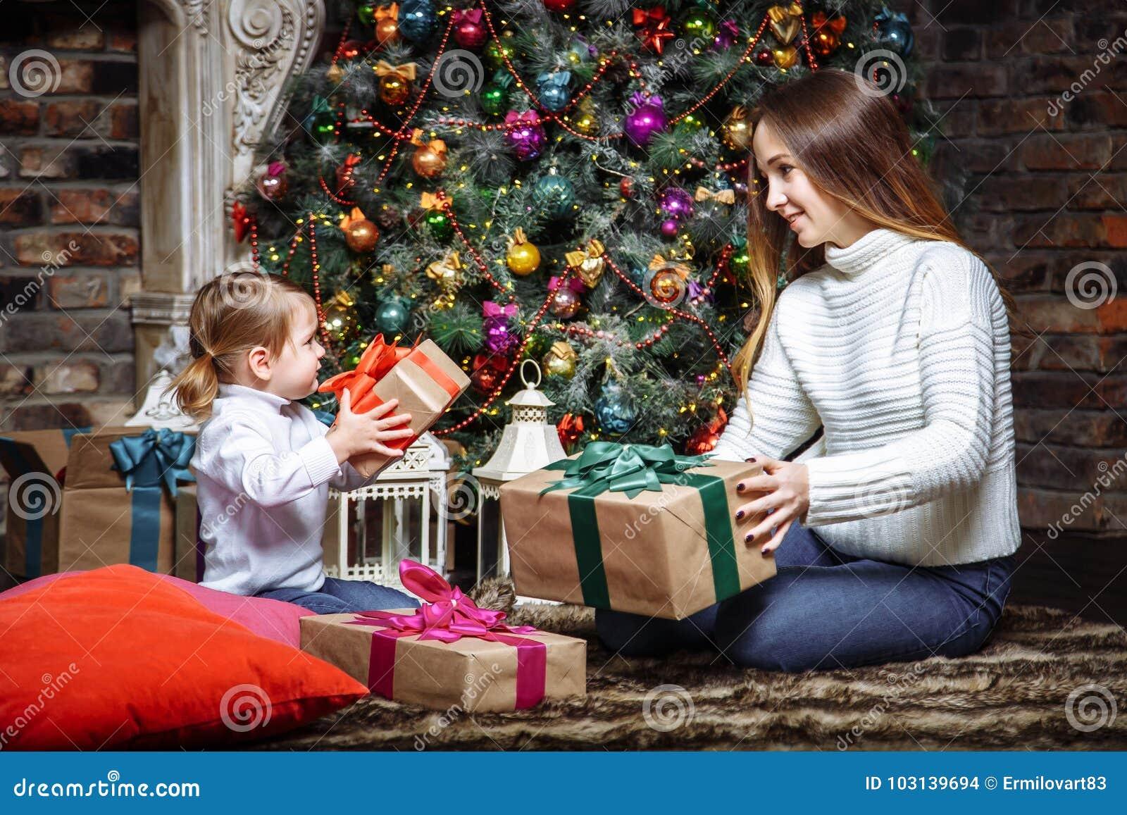 圣诞快乐和节日快乐!快乐的交换礼物的妈妈和她逗人喜爱的女儿 父母和小孩获得乐趣在C附近