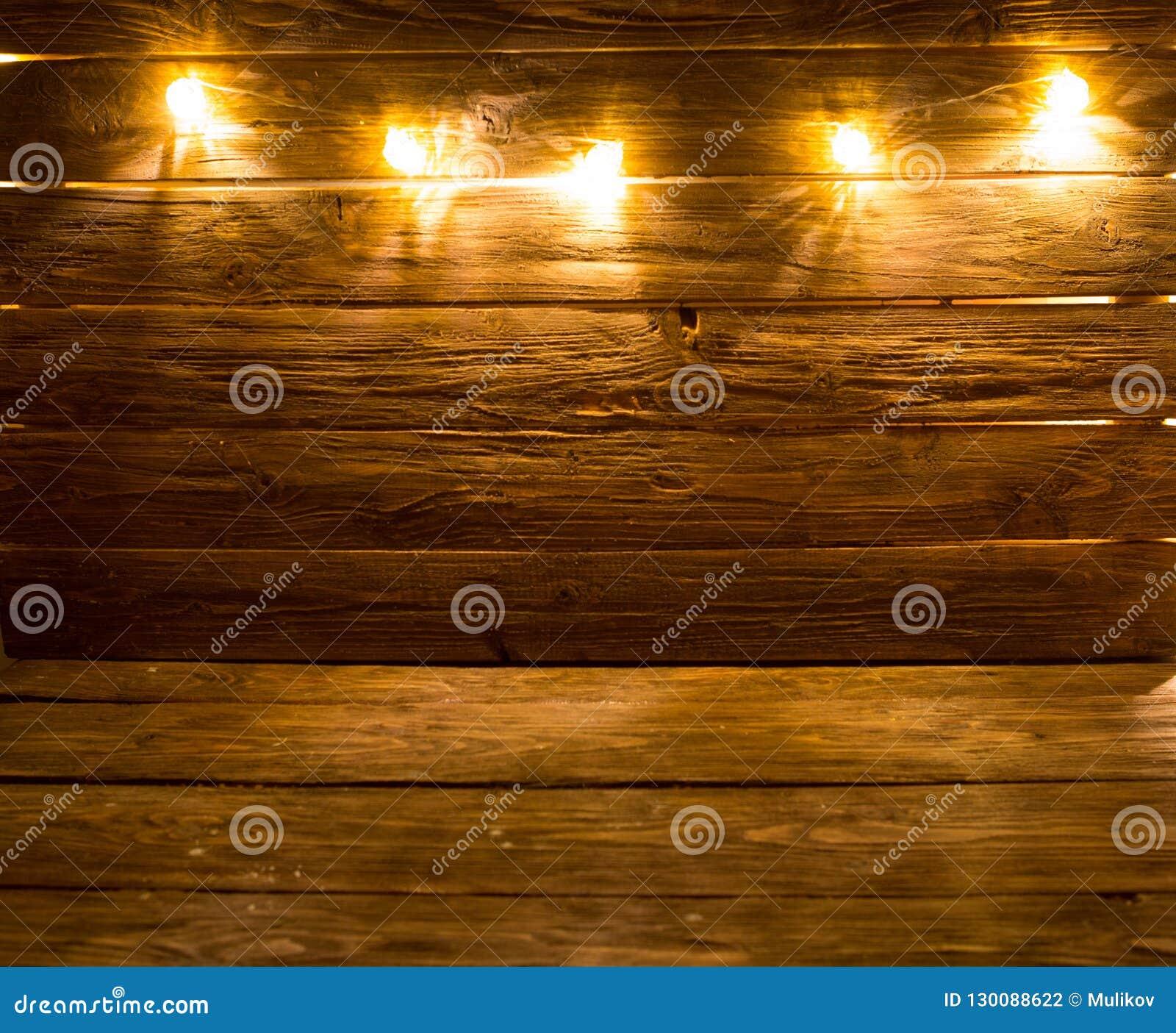 圣诞快乐!在棕色土气木背景的圣诞灯背景