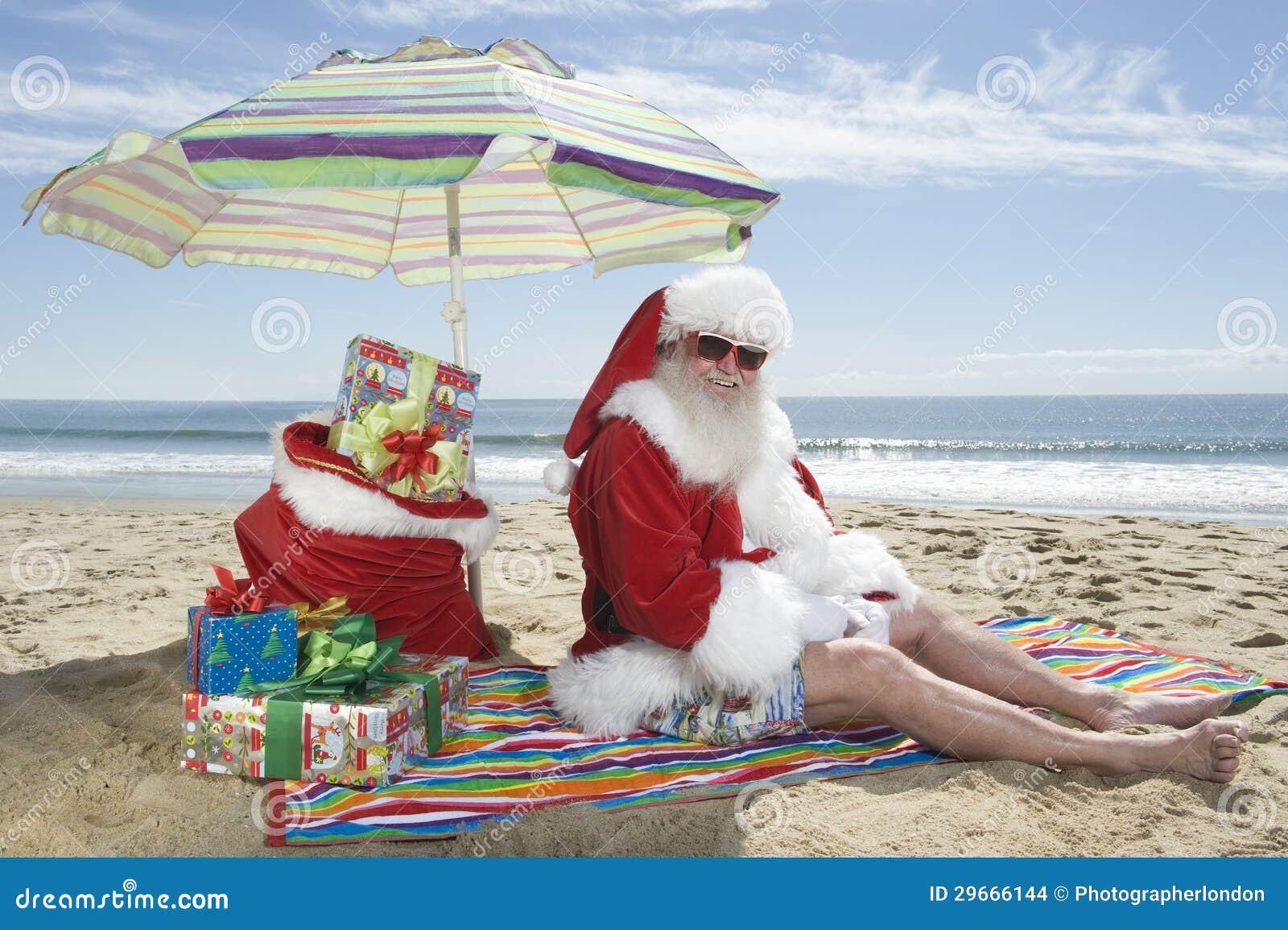 圣诞老人在有礼物的遮阳伞下坐海滩