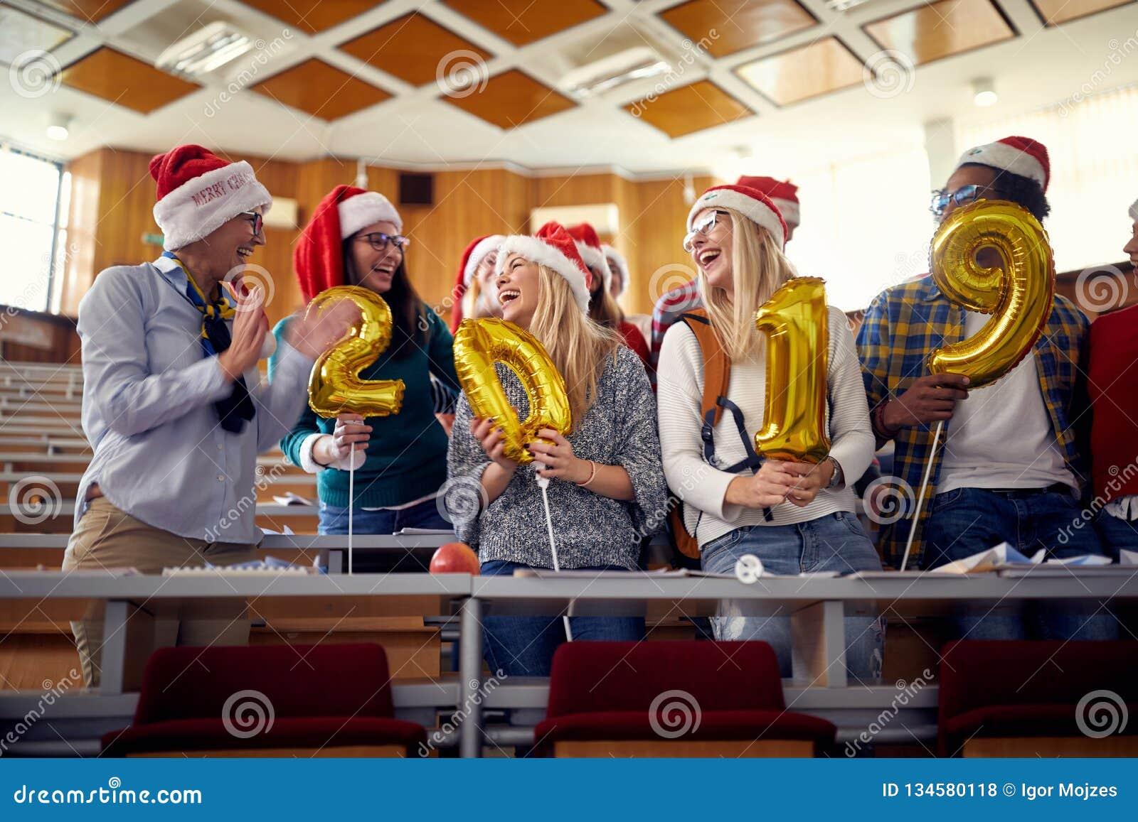 圣诞老人帽子的愉快的同事 获得乐趣在大学的新年庆祝