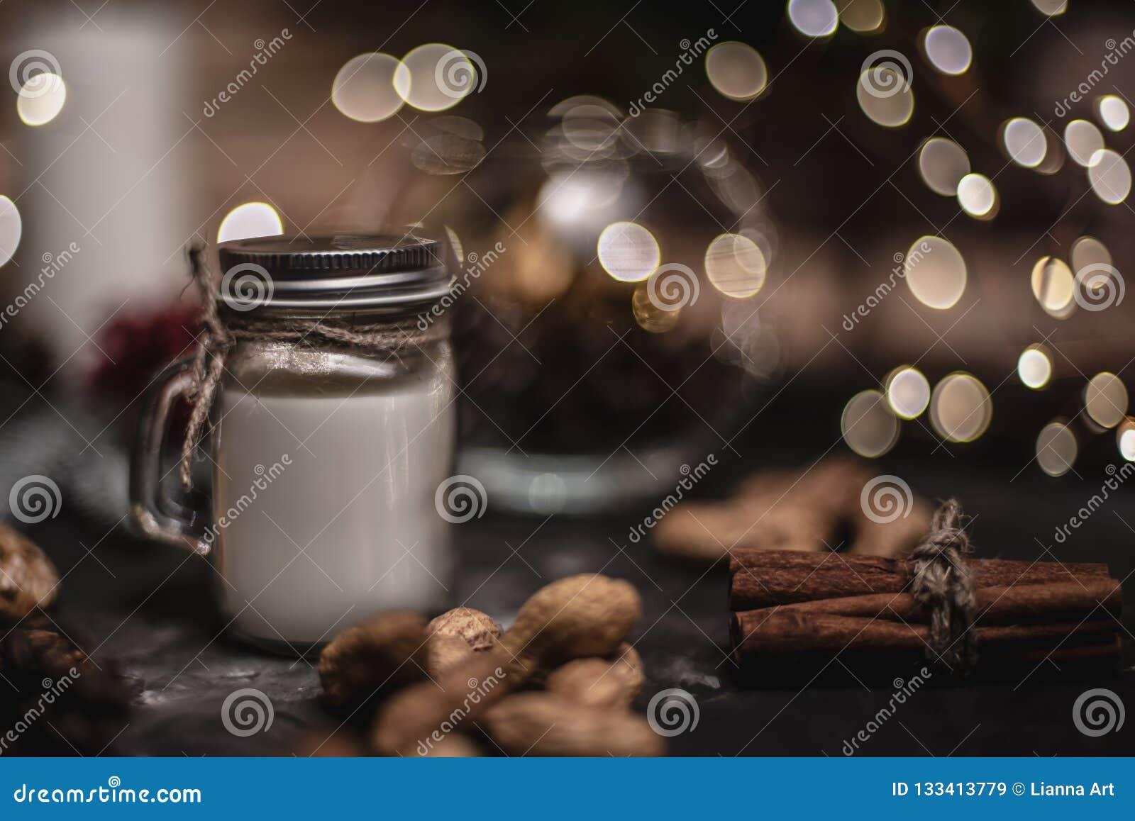 圣诞节和新年与圆的bokeh诗歌选、桂香、曲奇饼、锥体、坚果和蜡烛的装饰背景在杯子