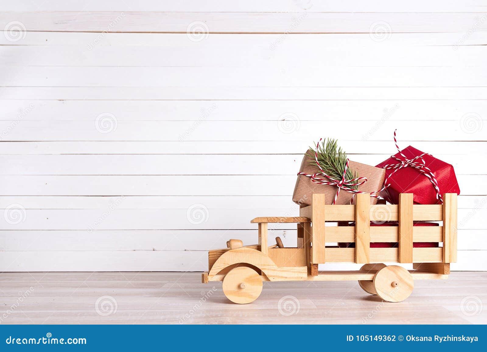 圣诞节在木玩具卡车的礼物盒在白色木backgro