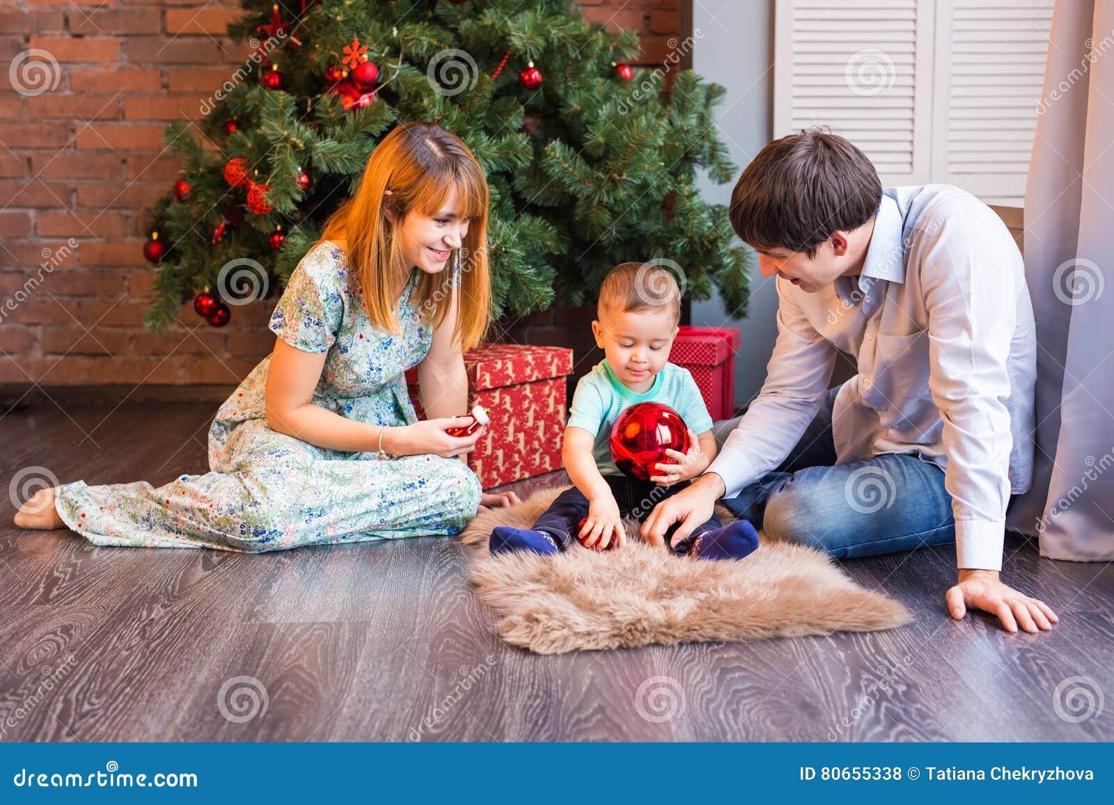 圣诞节家庭画象在家庭假日客厅,装饰由Xmas树的议院对光检查诗歌选