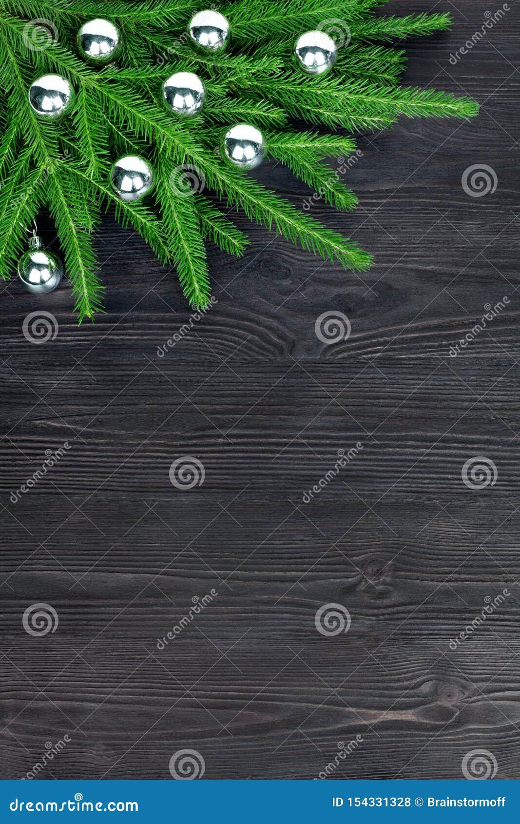 圣诞节欢乐壁角边界,新年装饰框架,在绿色冷杉分支的银色玻璃球装饰在黑木头