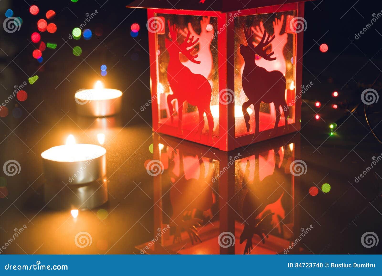 圣诞节灯笼和茶轻的蜡烛与bokeh光在黑背景