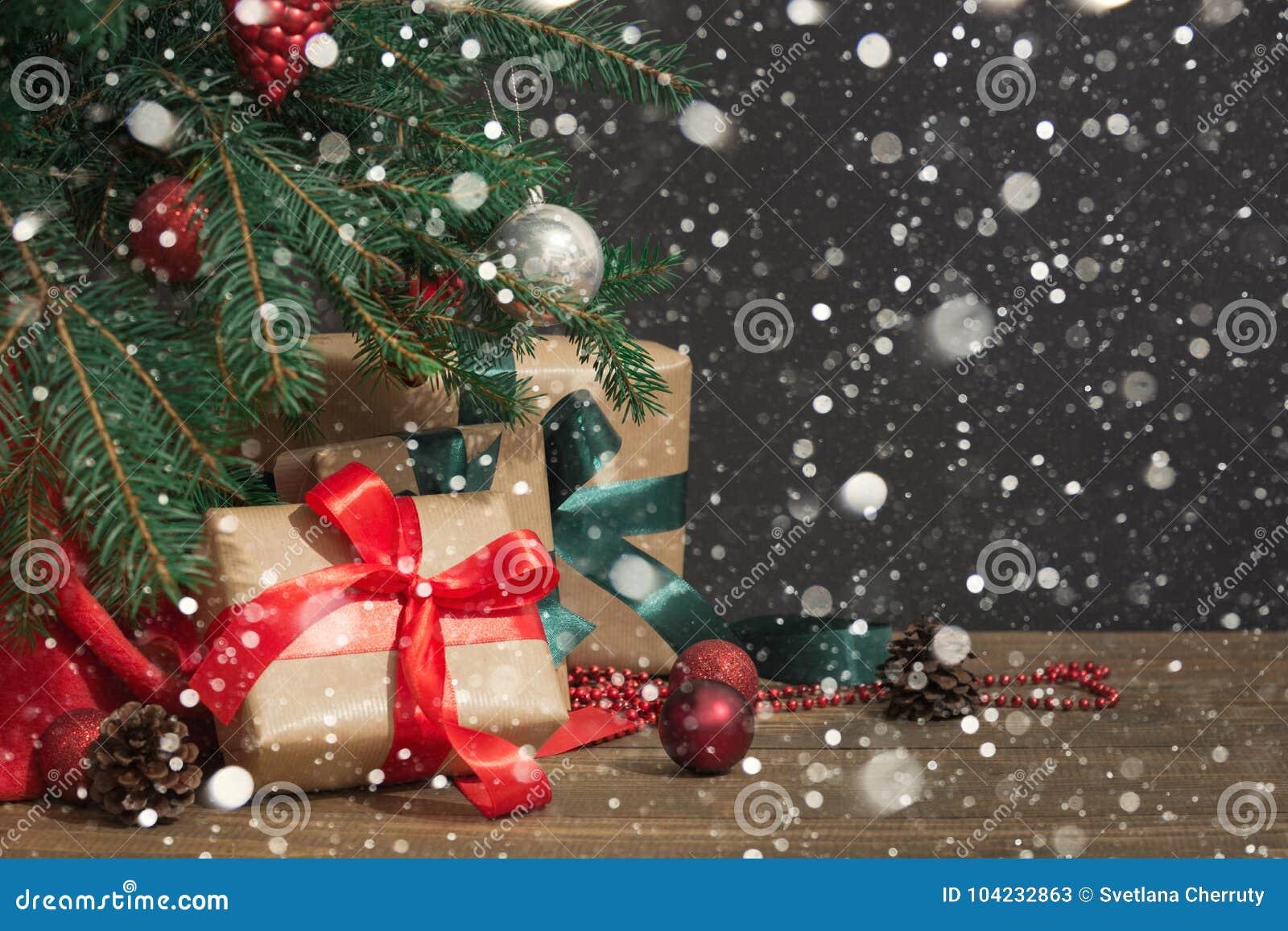 圣诞节节假日背景 与一个红色丝带,圣诞老人` s帽子和装饰的礼物在一个木板的一棵圣诞树下