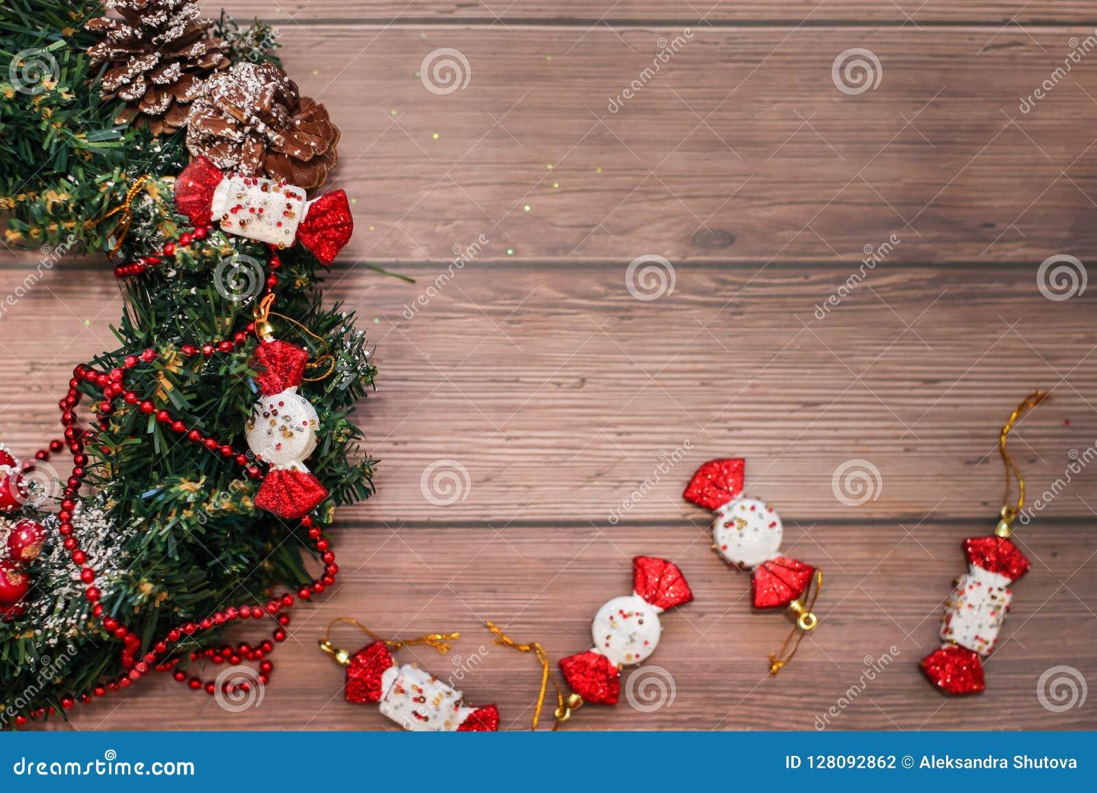 圣诞节花圈和在木桌上的红色装饰平的位置与爆沸的 假日圣诞节和新年背景