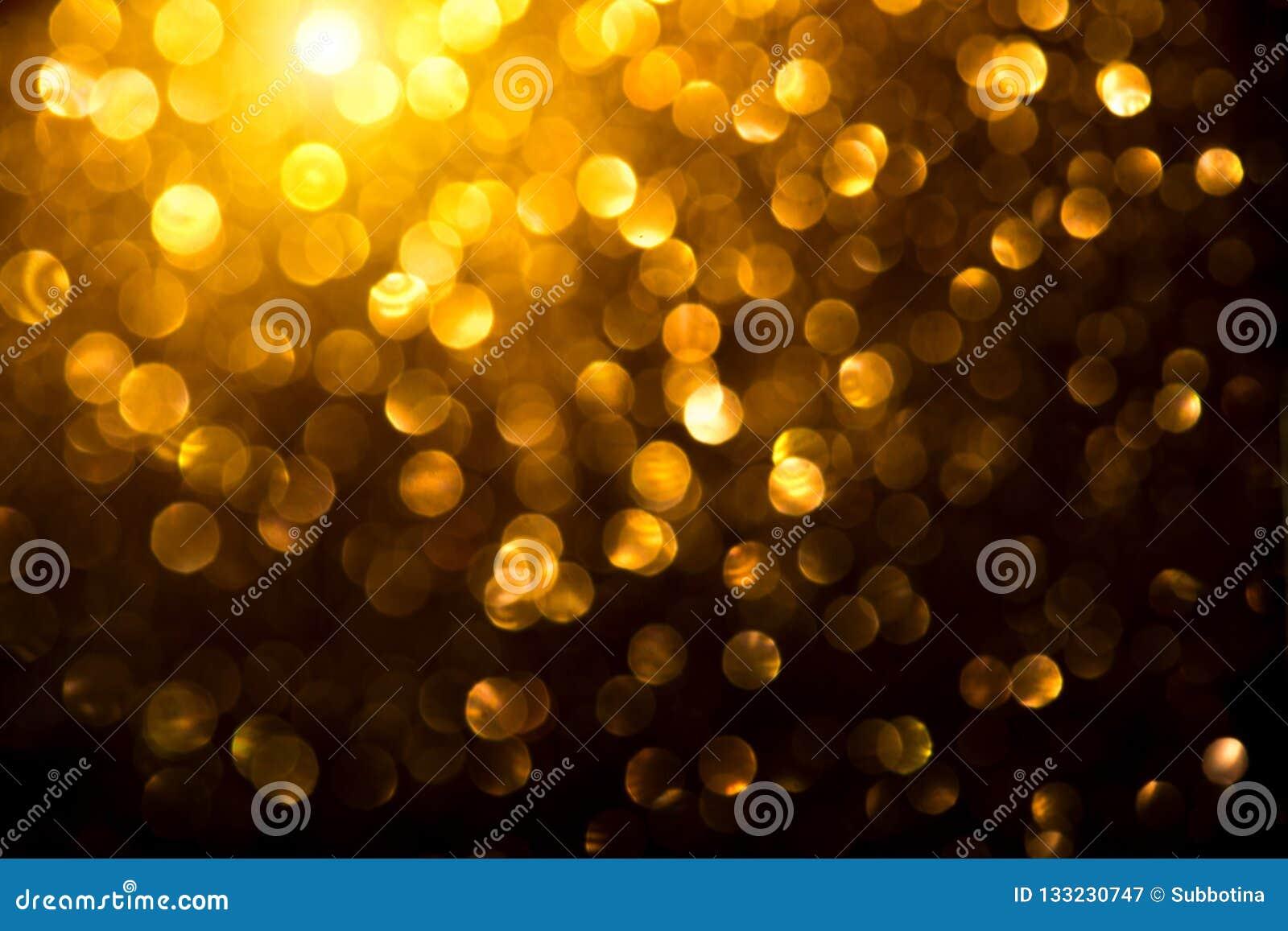 圣诞节金黄发光的背景 假日摘要defocused背景 闪亮金属片在黑色的被弄脏的金bokeh