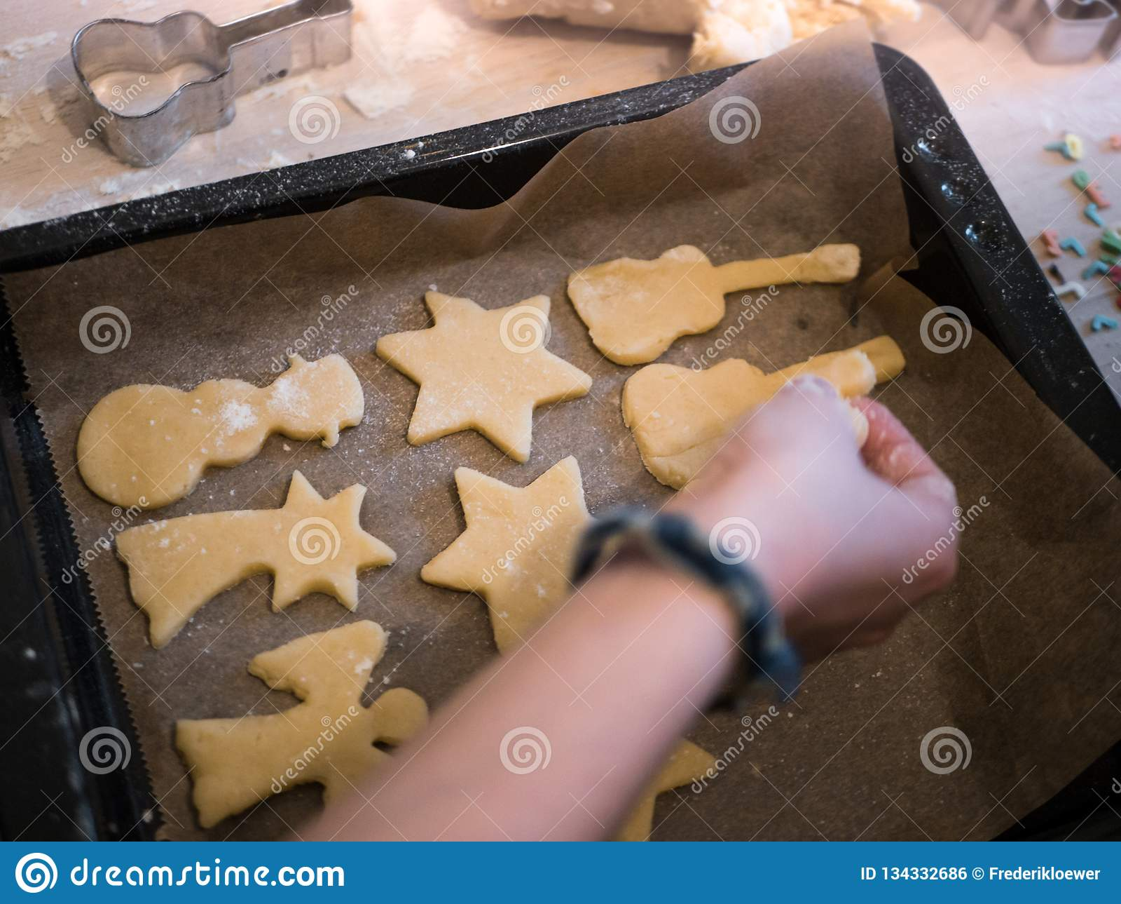 圣诞节面包店:投入曲奇饼面团的不同的形状女孩在一个烘烤的盘子
