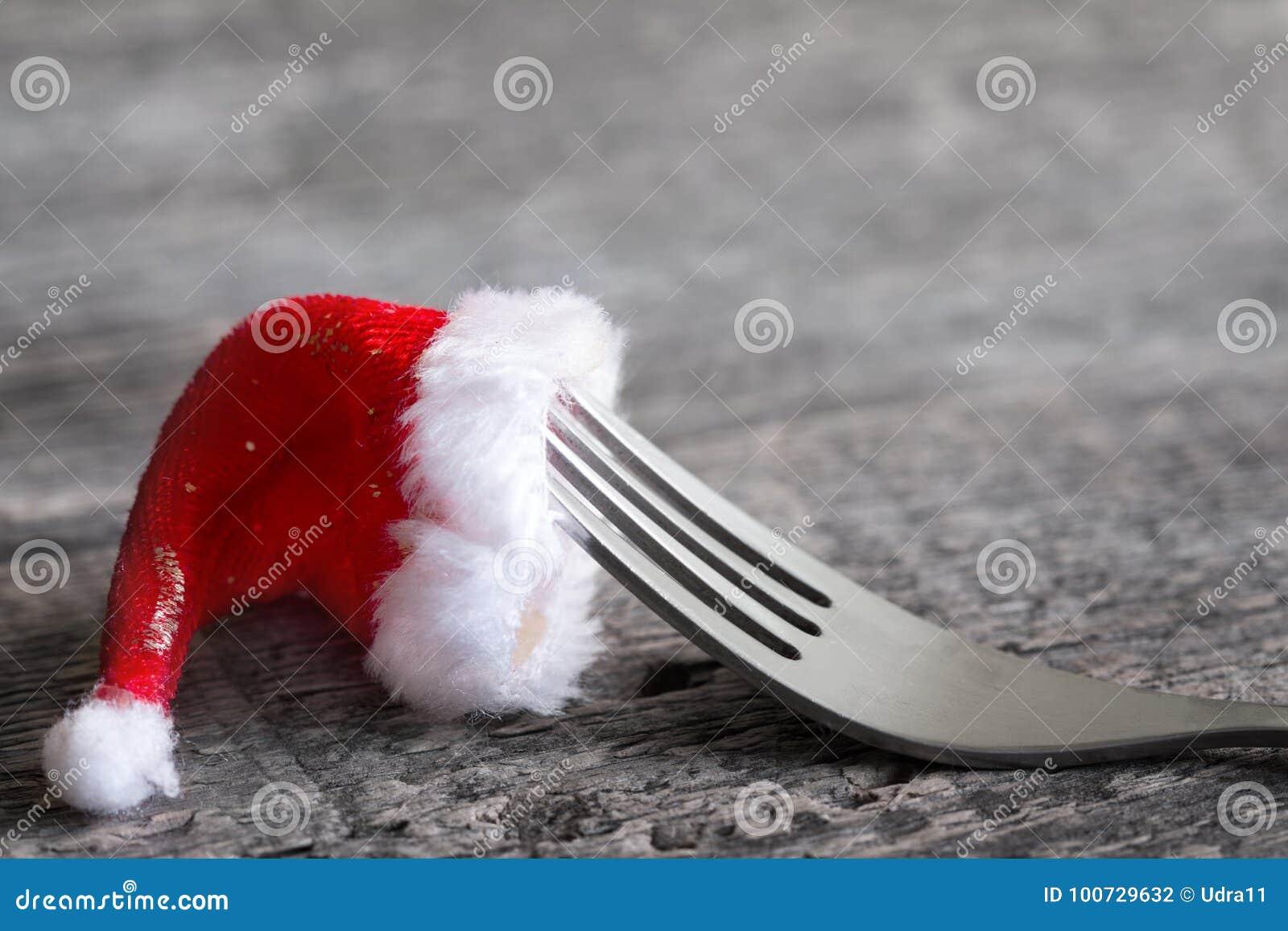 圣诞节食物菜单与叉子的摘要背景和在桌上的圣诞老人帽子