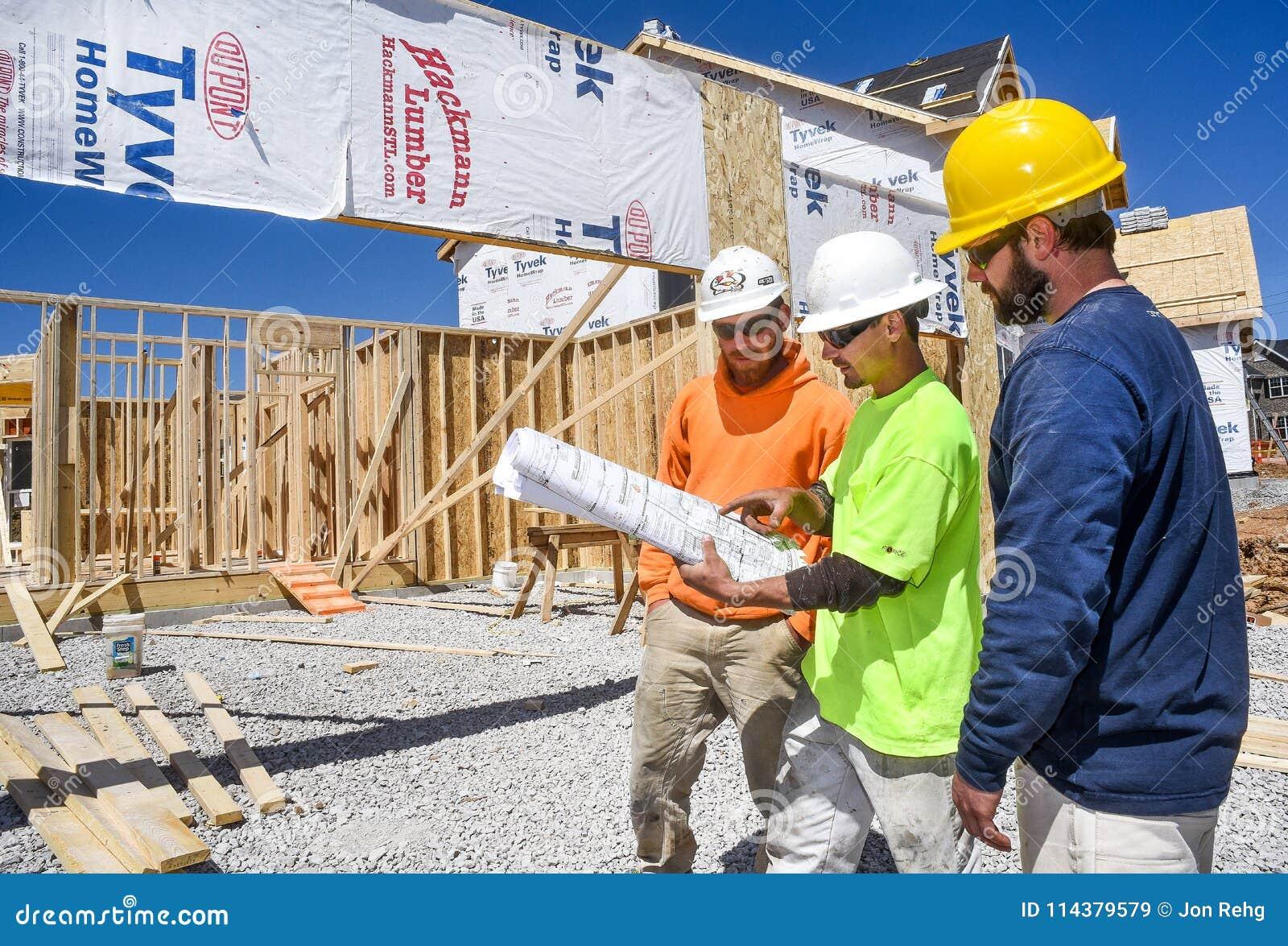圣路易斯,密苏里,团结状态4月4日, 2018-Three邮件建筑工人,木匠,佩带的安全帽看图纸